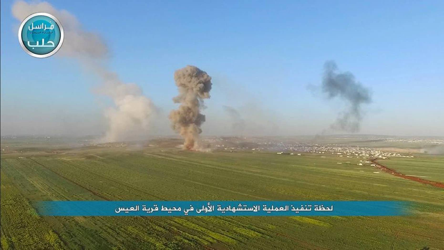 """In this image posted on the Twitter page of Syria's al-Qaida-linked Nusra Front on Friday, April 1, 2016, shows smoke billowing as Nusra Front fighters attack the northern village of al-Ais in Aleppo province, Syria. The Britain-based Syrian Observatory for Human Rights says 12 Hezbollah fighters were killed and dozens were wounded in Saturday's attack by militants led by al-Qaida's Syria branch — known as the Nusra Front — on the northern village of al-Ais.  The title in Arabic that reads """"the moment the first martyrdom operation occurred near the village of al-Ais."""" (Al-Nusra Front via AP)"""