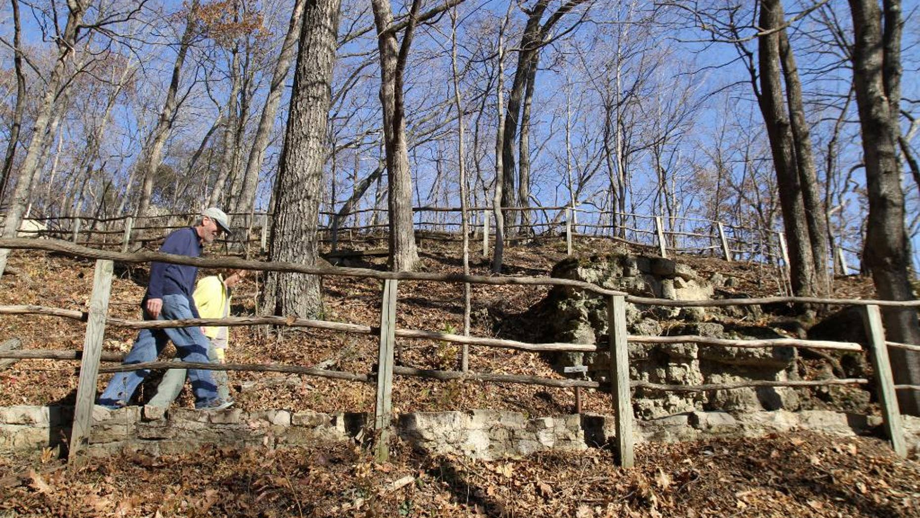 FILE - In this Nov. 8, 2010, file photo, pedestrians hike one of the trails at Effigy Mounds National Monument in Harpers Ferry, Iowa. Thomas Munson, the former superintendent of the monument, is scheduled to be sentenced Friday, July 8, 2016, in Cedar Rapids for stealing the remains of Native Americans who died hundreds of years ago. He's admitted to stealing a collection of ancient bones in 1990 and stashing them in his garage for two decades. (Justin Hayworth/The Des Moines Register via AP, File)