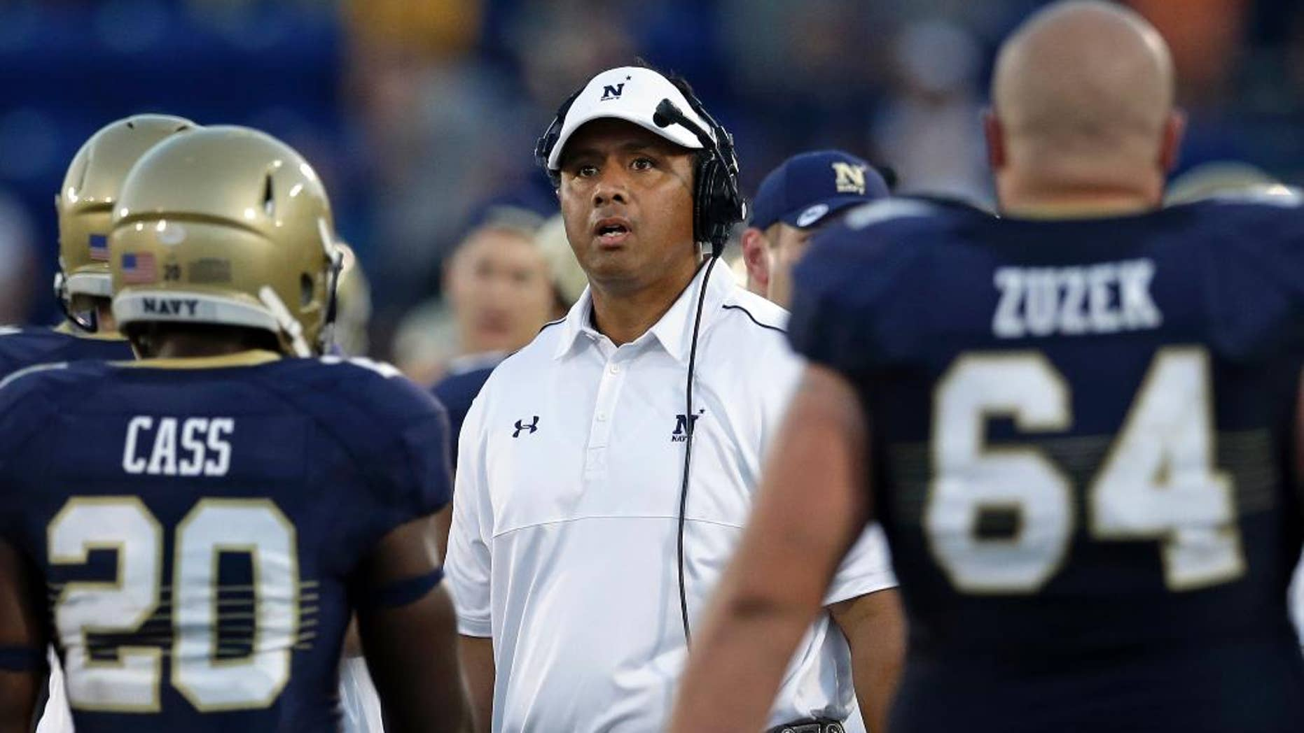 Navy head coach Ken Niumatalolo, center, looks on as players walk off the field after Navy's touchdown attempt on fourth down went out of bounds in the final moments of an NCAA college football game against Rutgers in Annapolis, Md., Saturday, Sept. 20, 2014. Rutgers won 31-24. (AP Photo/Patrick Semansky)