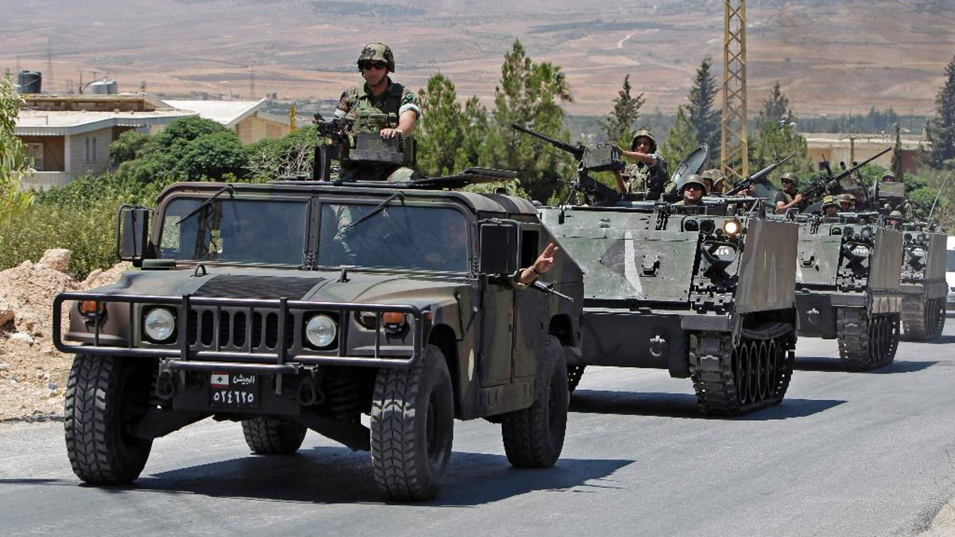 FILE - In this Aug. 4, 2014, file photo, Lebanese army reinforcements arrive at an area on the outskirts of Arsal, a predominantly Sunni Muslim town near the Syrian border in eastern Lebanon. A roadside bomb exploded near an army patrol in Arsal, wounding at least three soldiers, the military said Friday, Nov. 14. (AP Photo/Bilal Hussein, File)