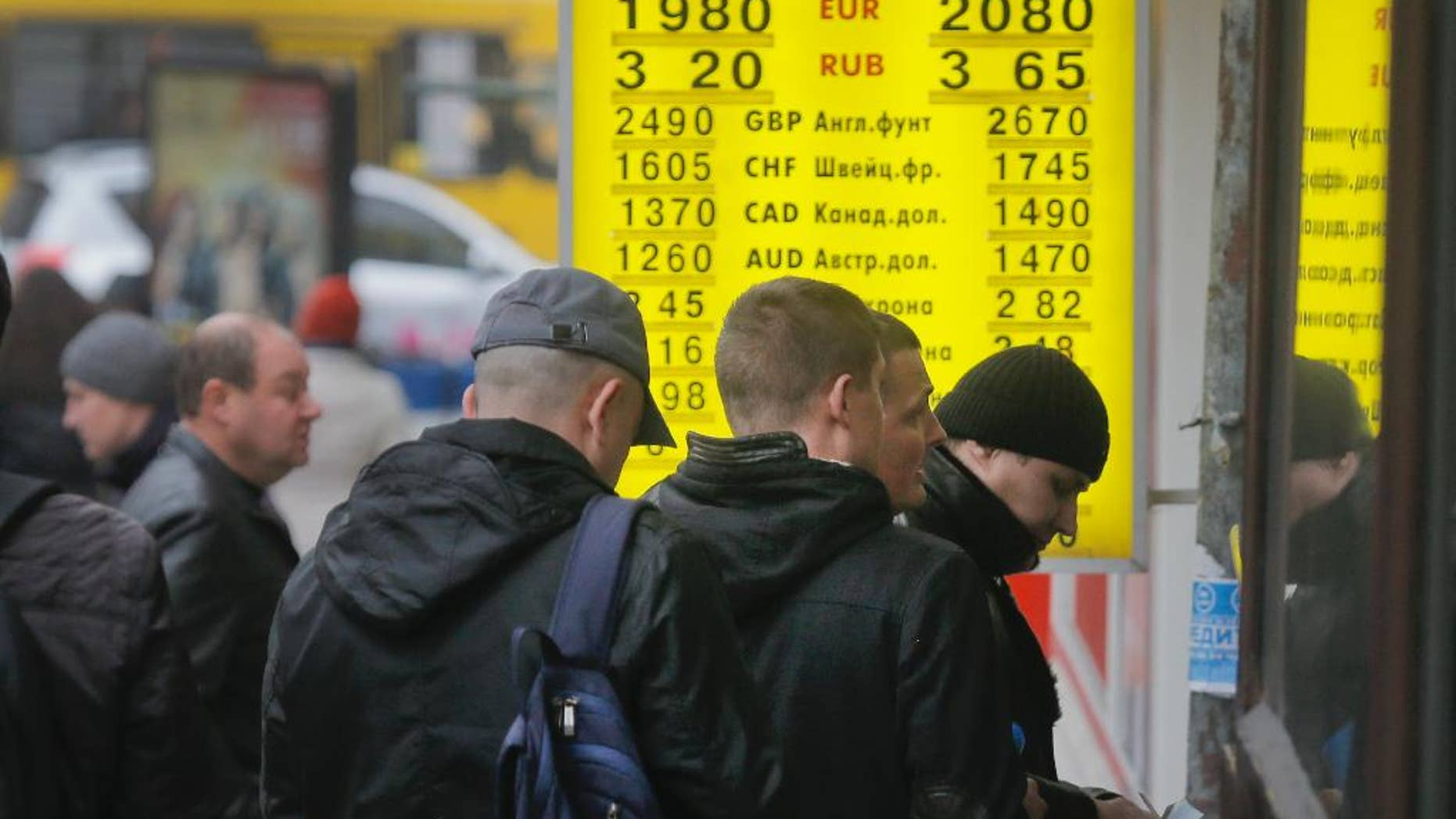 People stand in line at a currency exchange bureau in Kiev, Ukraine, Thursday, Nov. 13, 2014.  Ukraine's hryvnia plunged to UAH 15.56/USD on Nov. 13, a 14% decline since Nov. 5, when the National Bank of Ukraine reduced its interventions at the ForEx and allowed further weakening. Ukraine's national currency has already lost nearly 47% of its value this year, falling from UAH 8.1/USD.  (AP Photo/Efrem Lukatsky)