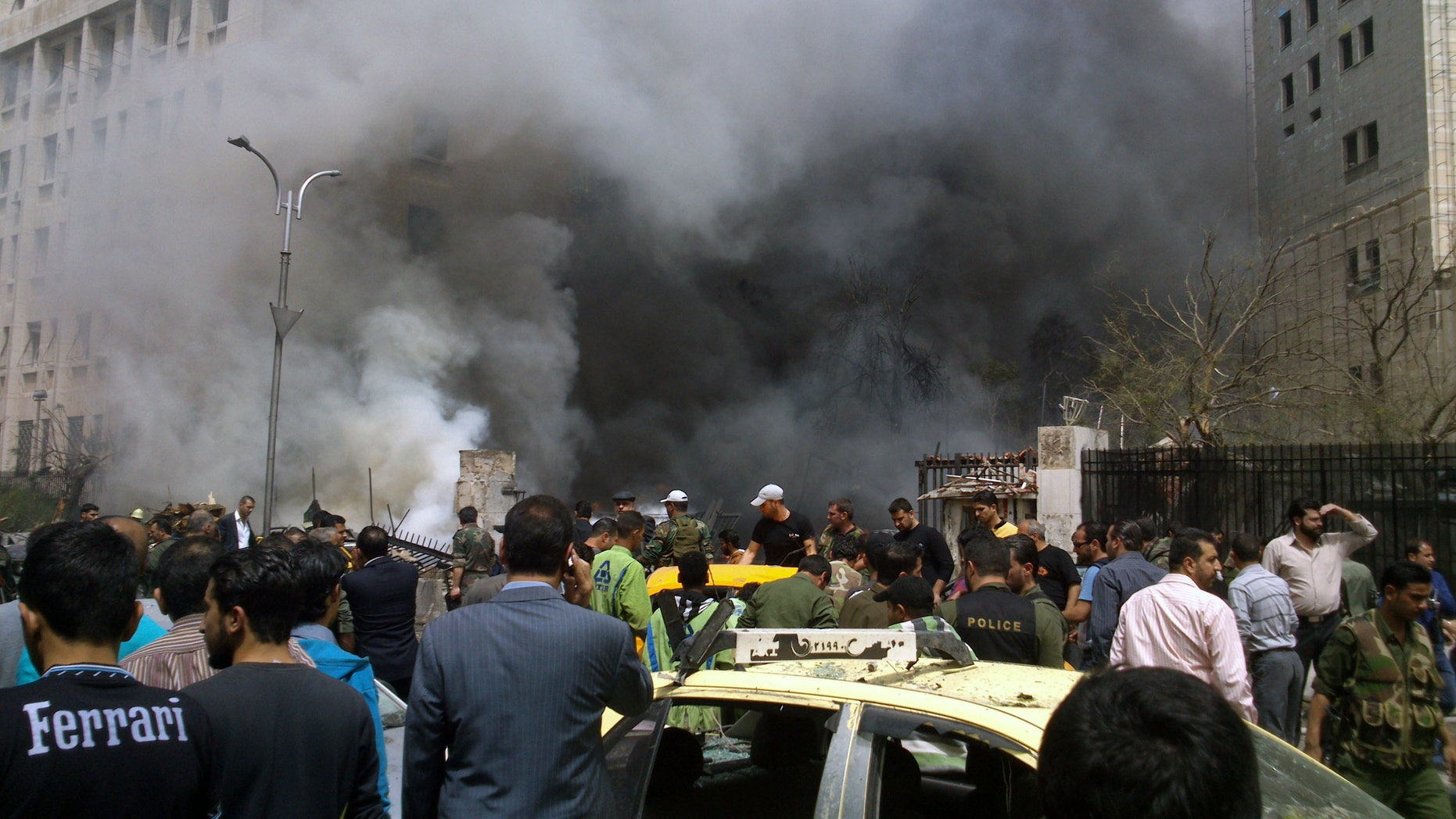 April. 8, 2013: This photo released by the Syrian official news agency SANA, shows smoke rising from burned cars after a huge explosion shook the Sabaa Bahrat Square, one of the capital's biggest roundabouts, in Damascus, Syria. A car bomb rocked a busy residential and commercial district in central Damascus on Monday, killing more than a dozen with many more injured and sending a huge cloud of black smoke billowing over the capital's skyline, Syrian state-run media said.