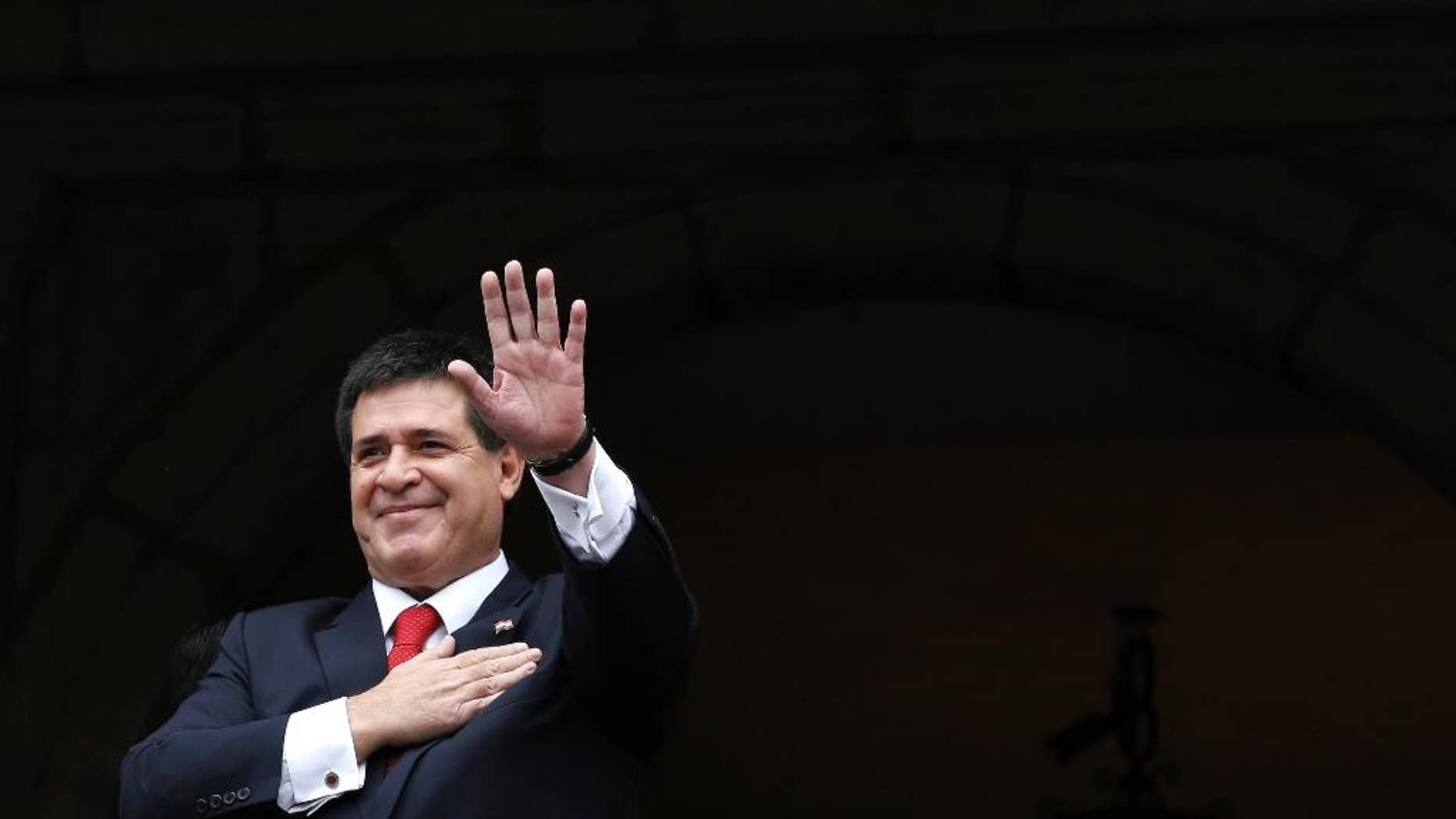 FILE - In this Nov. 21, 2014 file photo, Paraguay's President Horacio Cartes waves from a government palace balcony, in Quito, Ecuador. President Cartes said Monday, April 17, 2017, that he will not be a candidate in the 2018 election even if Congress approves a constitutional amendment to allow a second term. (AP Photo/Dolores Ochoa, File)