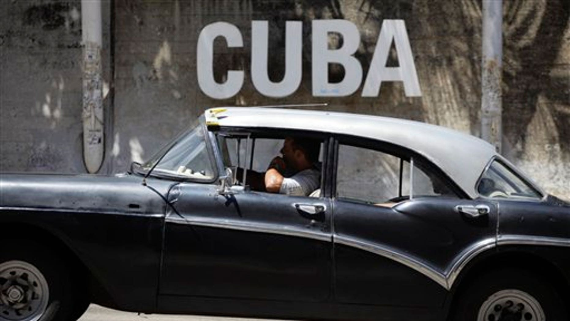 """A man drives his taxi past a Cultural Center with the word """"Cuba"""" on it, in Havana, Cuba, Tuesday, April 14, 2015."""