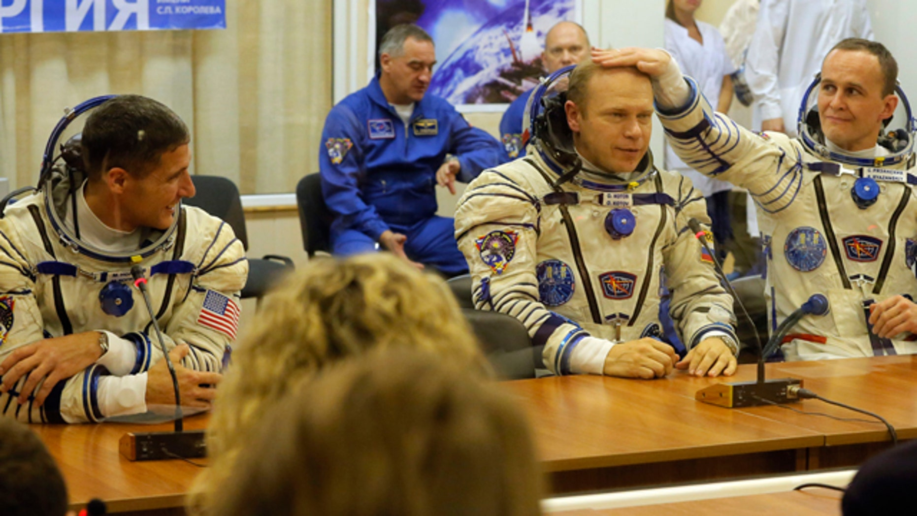 Sept. 26, 2013: U.S. astronaut Michael Hopkins, Russian cosmonauts Oleg Kotov and Sergey Ryazanskiy, crew members of the mission to the International Space Station, ISS, speak with their familys prior the launch of Soyuz-FG  rocket.