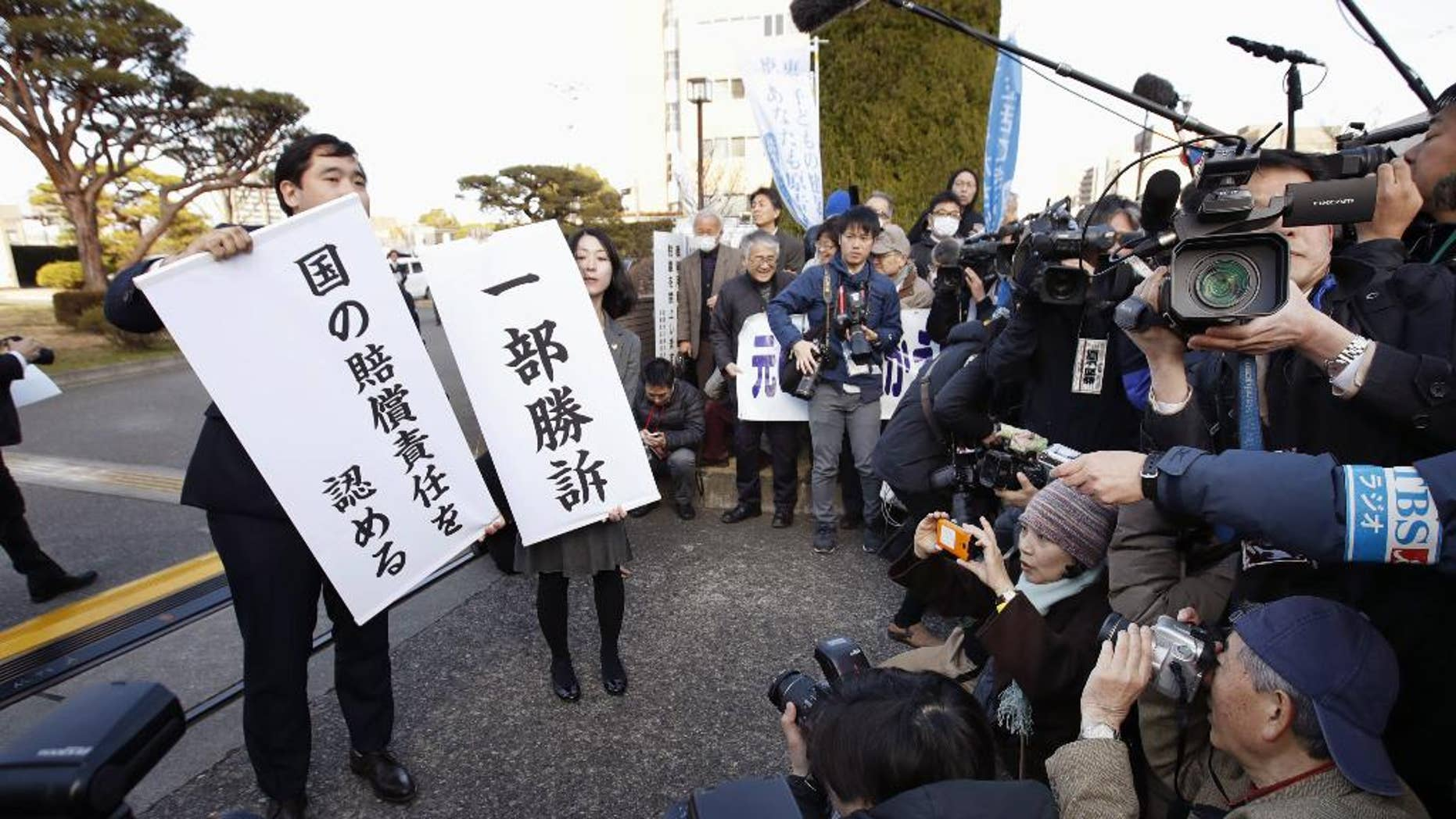 """Lawyers for a group of evacuees who were forced to leave their homes near the Fukushima nuclear plant display signs that read """"partially won a case,"""" right, and """"the government is liable"""" in front of the Maebashi District Court in Maebashi, north of Tokyo, Friday, March 17, 2017. The court Friday held Japan's government and a utility liable for neglecting tsunami safety measures at the Fukushima nuclear plant and ordered them to pay 62 of the thousands of people who fled radiation released during the March 2011 disaster. (Fumine Tsutabayashi/Kyodo News via AP)"""