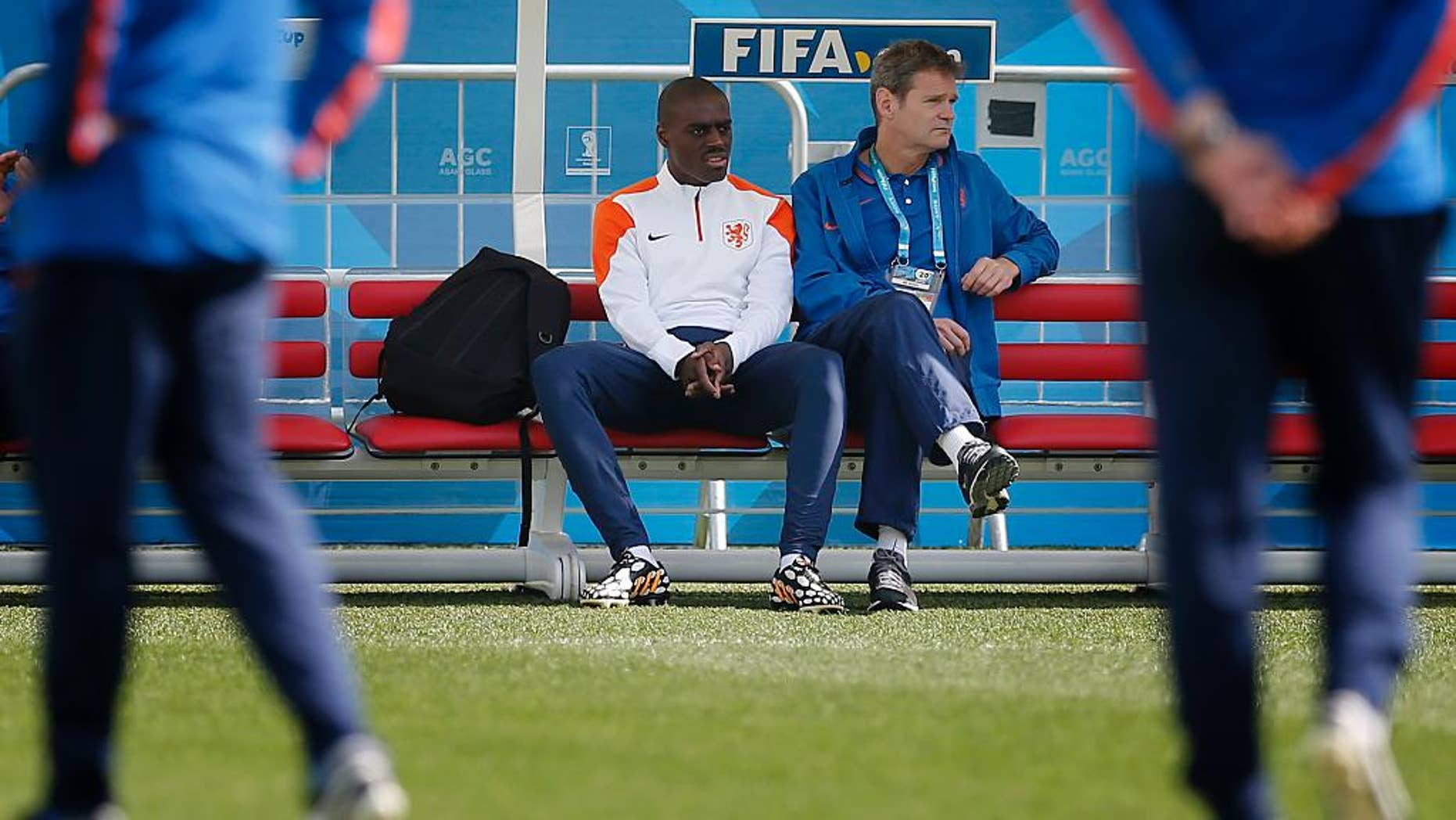Bruno Martins Indi, left, of the Netherlands sits out of a training session at the Itaquerao Stadium in Sao Paulo, Brazil, Sunday, June 22, 2014.  The Netherlands will play Chile in a match that will decide the winner of Group B at the 2014 soccer World Cup. (AP Photo/Wong Maye-E)