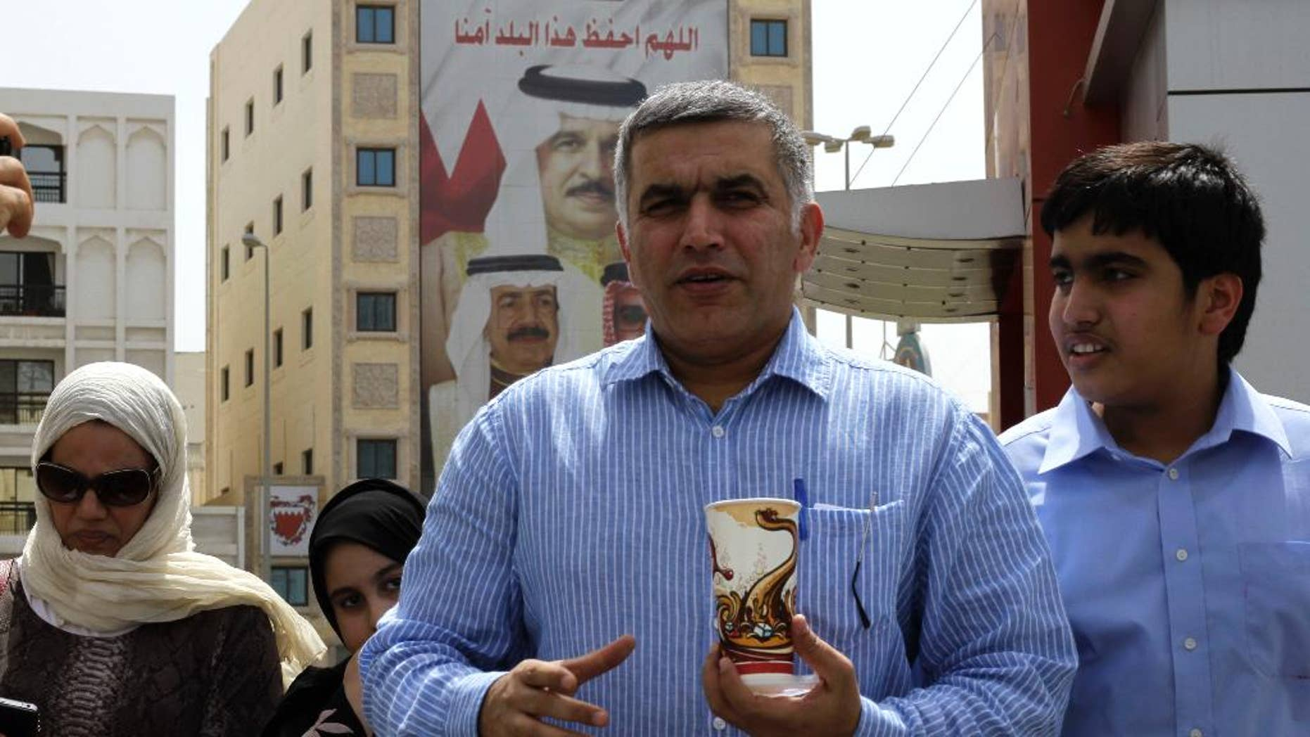 """This May 28, 2011 photo, Bahraini human rights activist Nabeel Rajab, center, accompanied by his wife Sumaya, left, daughter Malak, second left, and son Adam, right, leaves a Manama, Bahrain, police station.   Rajab was formally charged on Thursday, Oct. 9, 2014,  with insulting the ministries of defense and interior. His court date was set for Oct. 19.  Rajab was detained Oct. 1 over his tweets alleging that Bahrain's security institutions were incubators for extremist ideology. His lawyer Jalila al-Sayed said he was also accused of """"intimidating"""" security forces.  (AP Photo/Hasan Jamali)"""