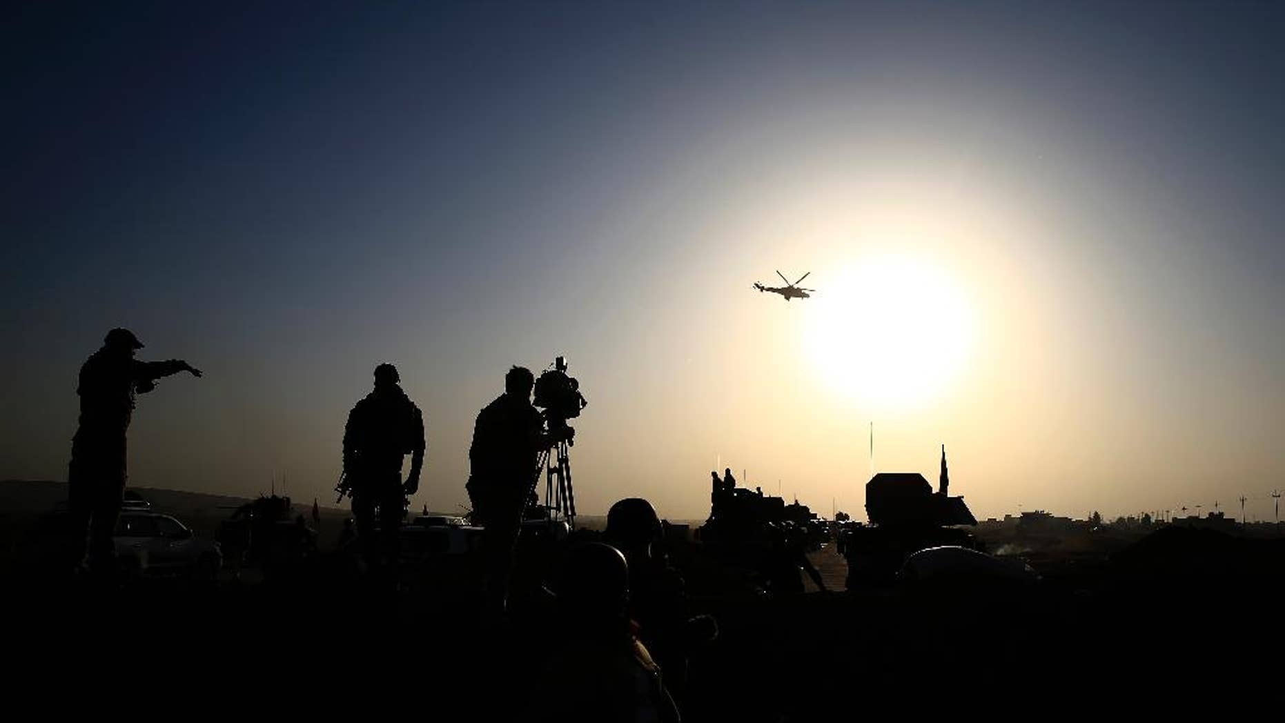 An Iraqi military helicopter flies over the frontline near Bartella, Iraq on Thursday, Oct. 20, 2016. Iraqi special forces charged into the Mosul battle Thursday with a pre-dawn advance on the nearby town held by the Islamic State group, a key part of a multi-pronged assault on eastern approaches to the besieged city. (AP Photo/Bram Janssen)