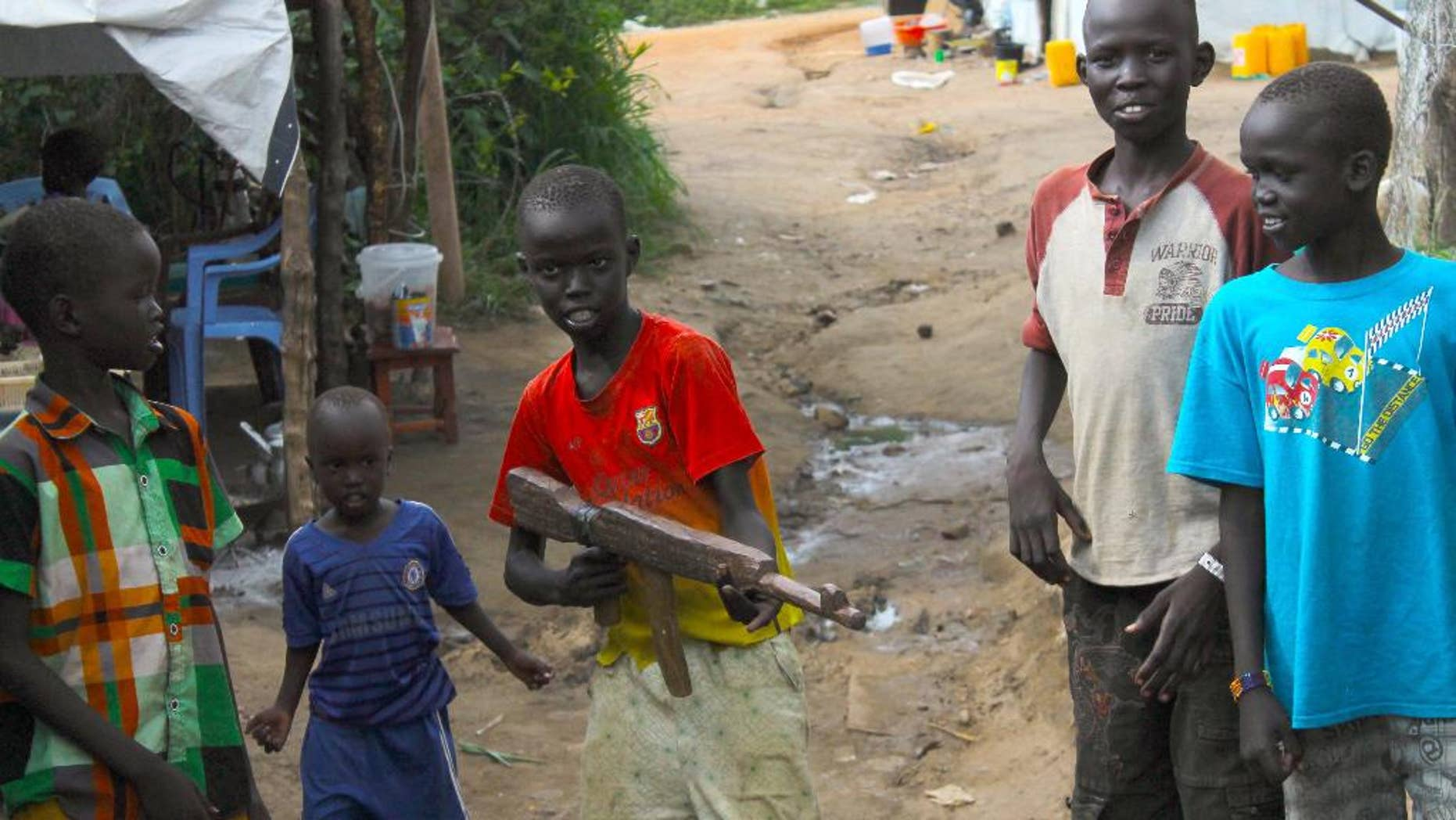In this Monday, July 25, 2016 photo, a group of children at the U.N. protection of Civilians site in Juba, South Sudan, play with a makeshift gun. South Sudan's government has recruited child soldiers in the past week to prepare for a renewed conflict, according to an internal United Nations document obtained by The Associated Press. The document says a senior politician appointed by President Salva Kiir led the recruitment of an entire village of boys using intimidation. Some were as young as 12 years old. It was not clear how many children were involved. (AP Photo/Justin Lynch)