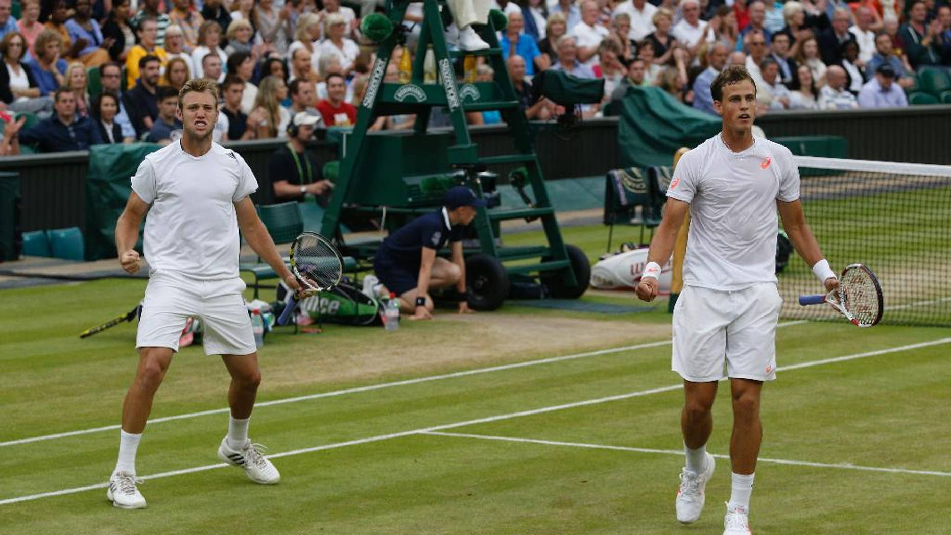 Vasek Pospisil of Canada, right, and Jack Sock of the U.S celebrate a point during the men's doubles final against Bob Bryan and Mike Bryan of the U.S at the All England Lawn Tennis Championships in Wimbledon, London, Saturday, July 5, 2014. (AP Photo/Pavel Golovkin)