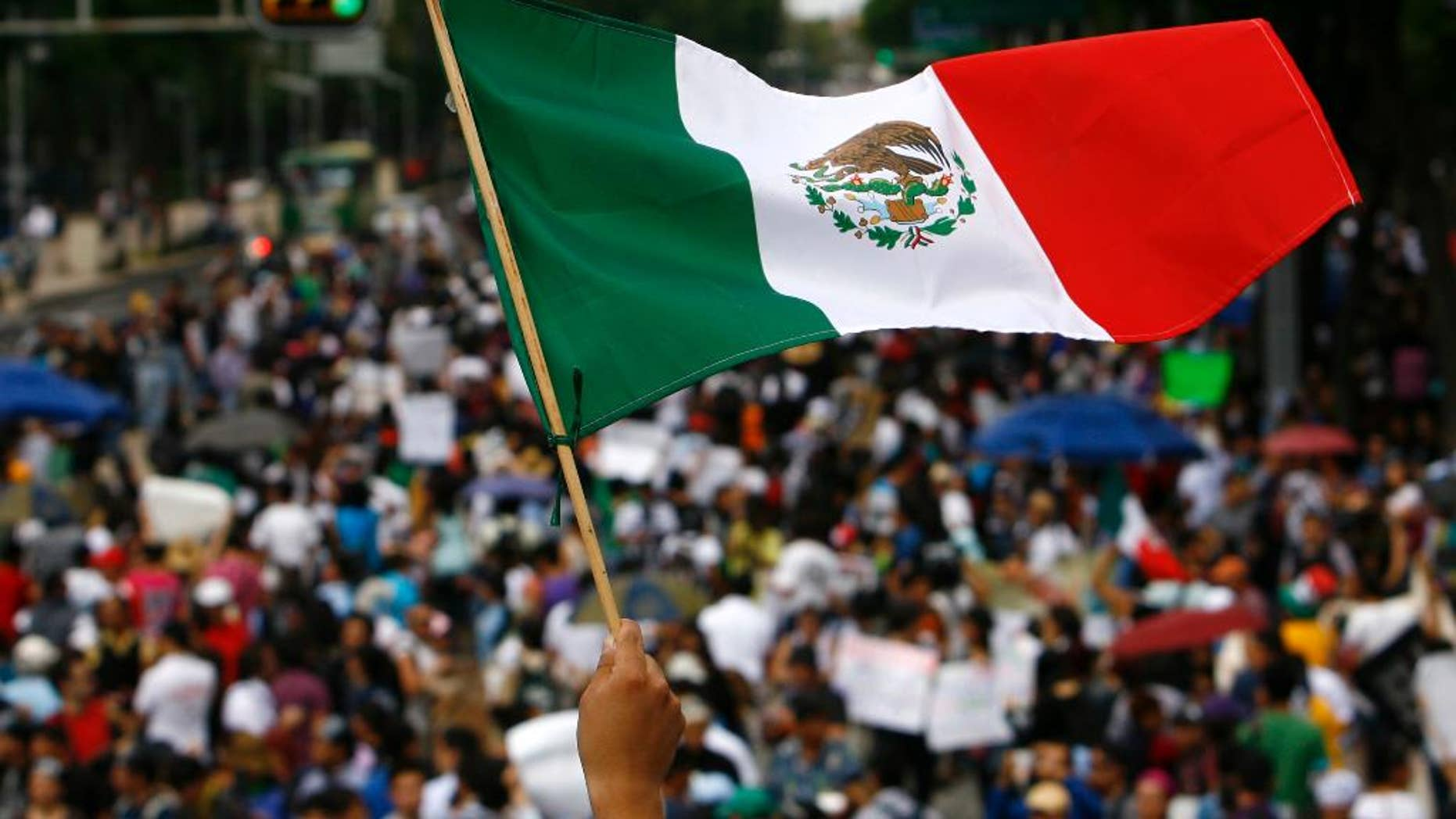 FILE - In this July 7, 2012 file photo, a woman waves a national flag as Mexicans march along Avenida Reforma on their way to Mexico City's main plaza, the Zocalo. The results of the last polls to be released before the Sunday, June 7, 2015 midterm elections show Mexico's ruling party appears poised to retain its leading position in congress, but may lose the ability to cobble together a majority with smaller parties. (AP Photo/Marco Ugarte, File)