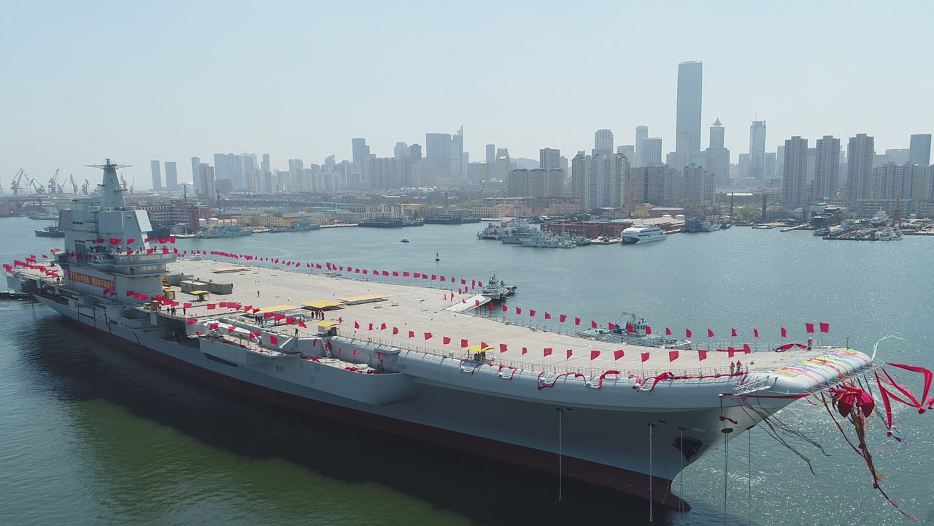 In this photo released by China's Xinhua News Agency, a newly-built aircraft carrier is transferred from dry dock into the water at a launch ceremony at a shipyard in Dalian in northeastern China's Liaoning Province, Wednesday, April 26, 2017.