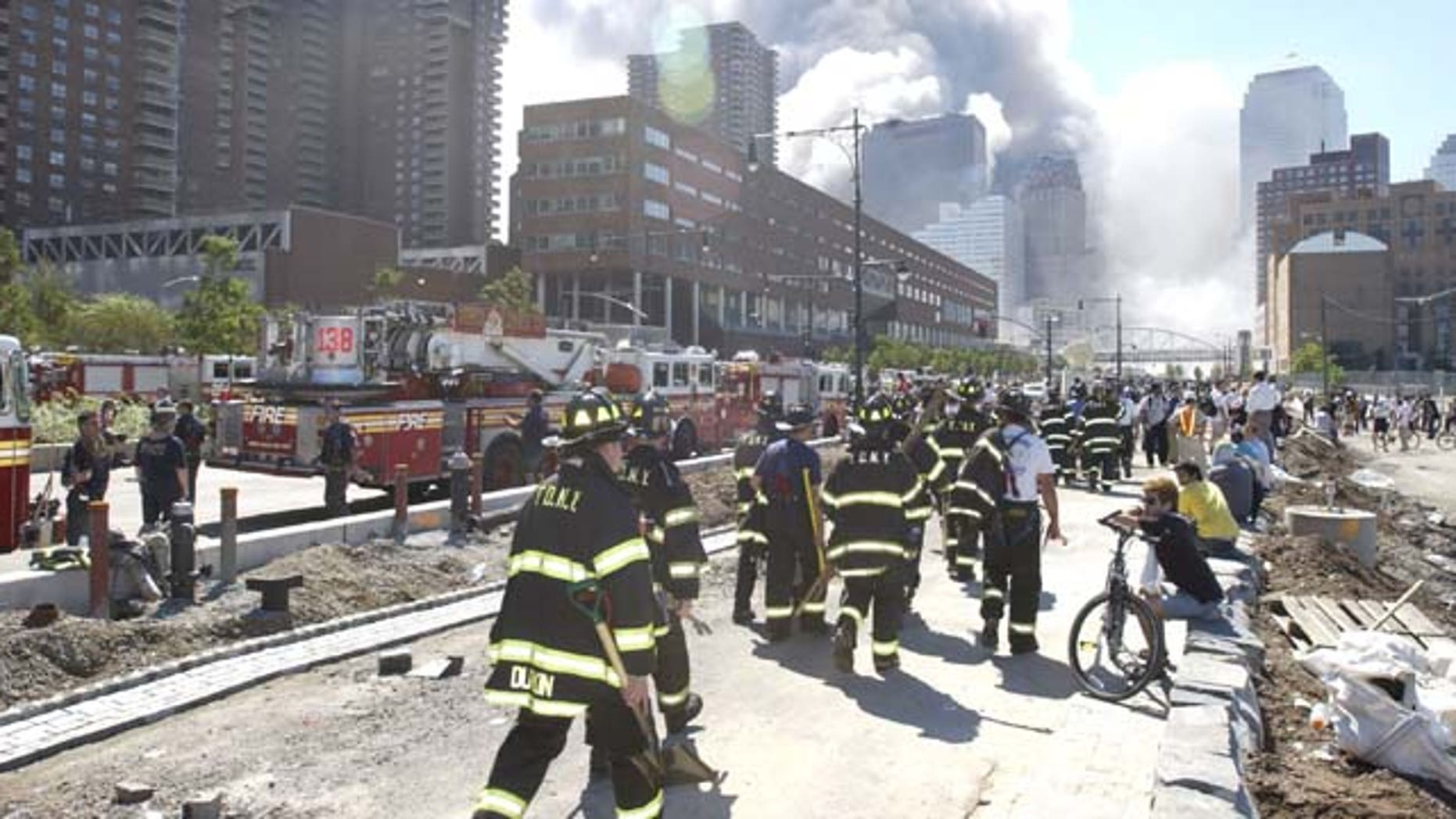 Fireman heading south on the West Side Highway towards the remains of the World Trade Center where smoke continued hours after the colapse. Streets of lower Manhattan with fireman, police, and rescue crews after the colapse of the World Trade Center after being hit by two airplanes on September 11, 2001.  photo by Gabe Palacio/ImageDirect