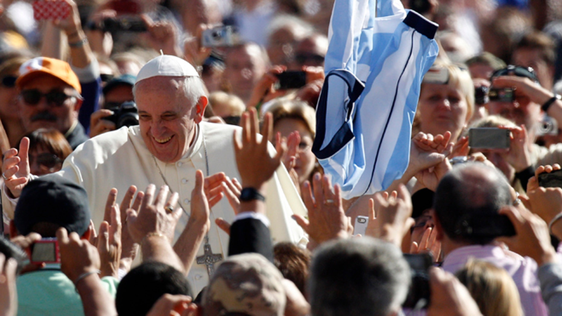 Pope Francis greets faithful upon arrival for his weekly general audience in St. Peter's Square at the Vatican, Wednesday, Sept. 18, 2013.