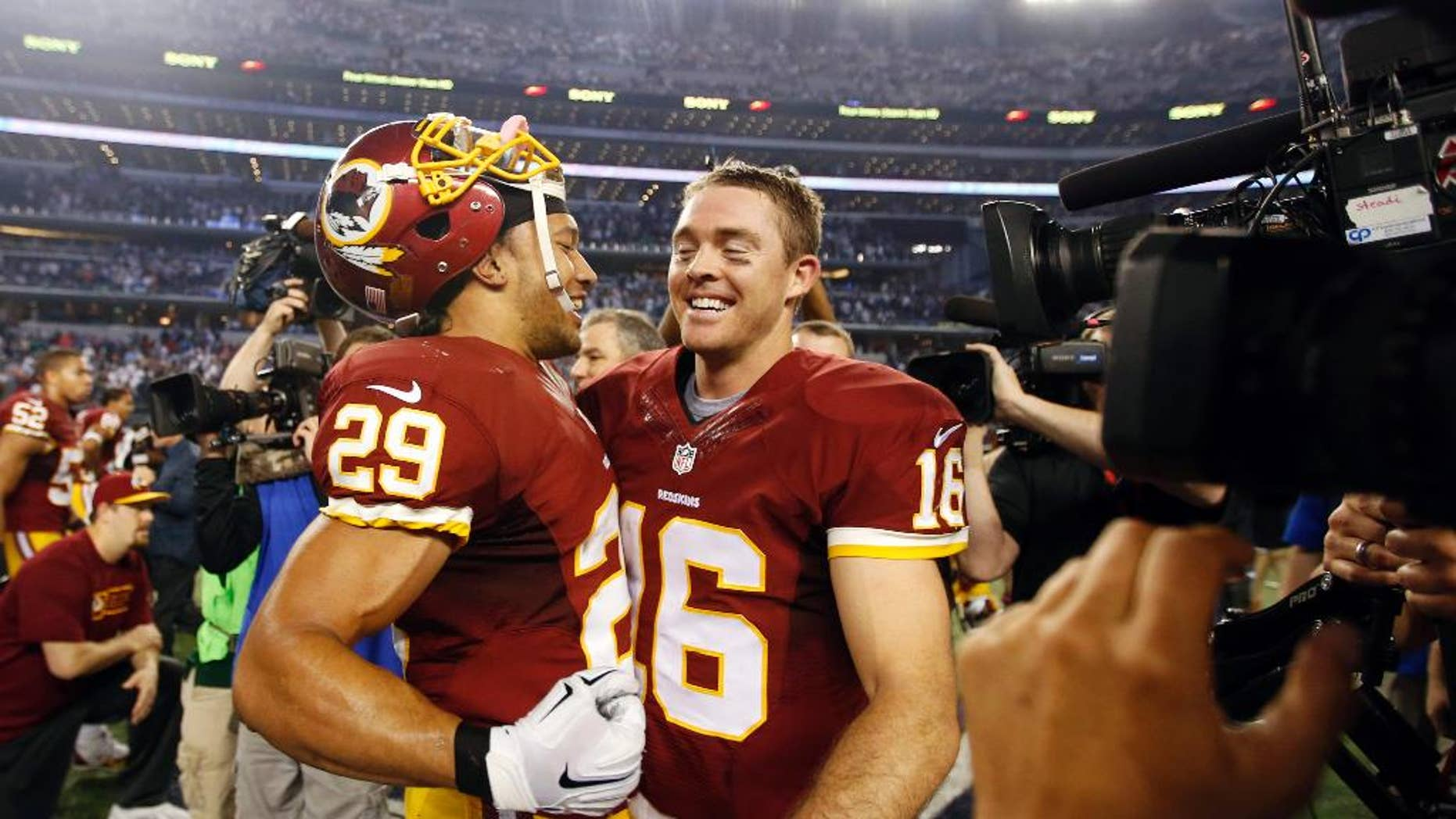 Washington Redskins' Roy Helu (29) and quarterback Colt McCoy (16) celebrate after an NFL football game against the Dallas Cowboys, Monday, Oct. 27, 2014, in Arlington, Texas. Washington won in overtime 20-17. (AP Photo/Tim Sharp)