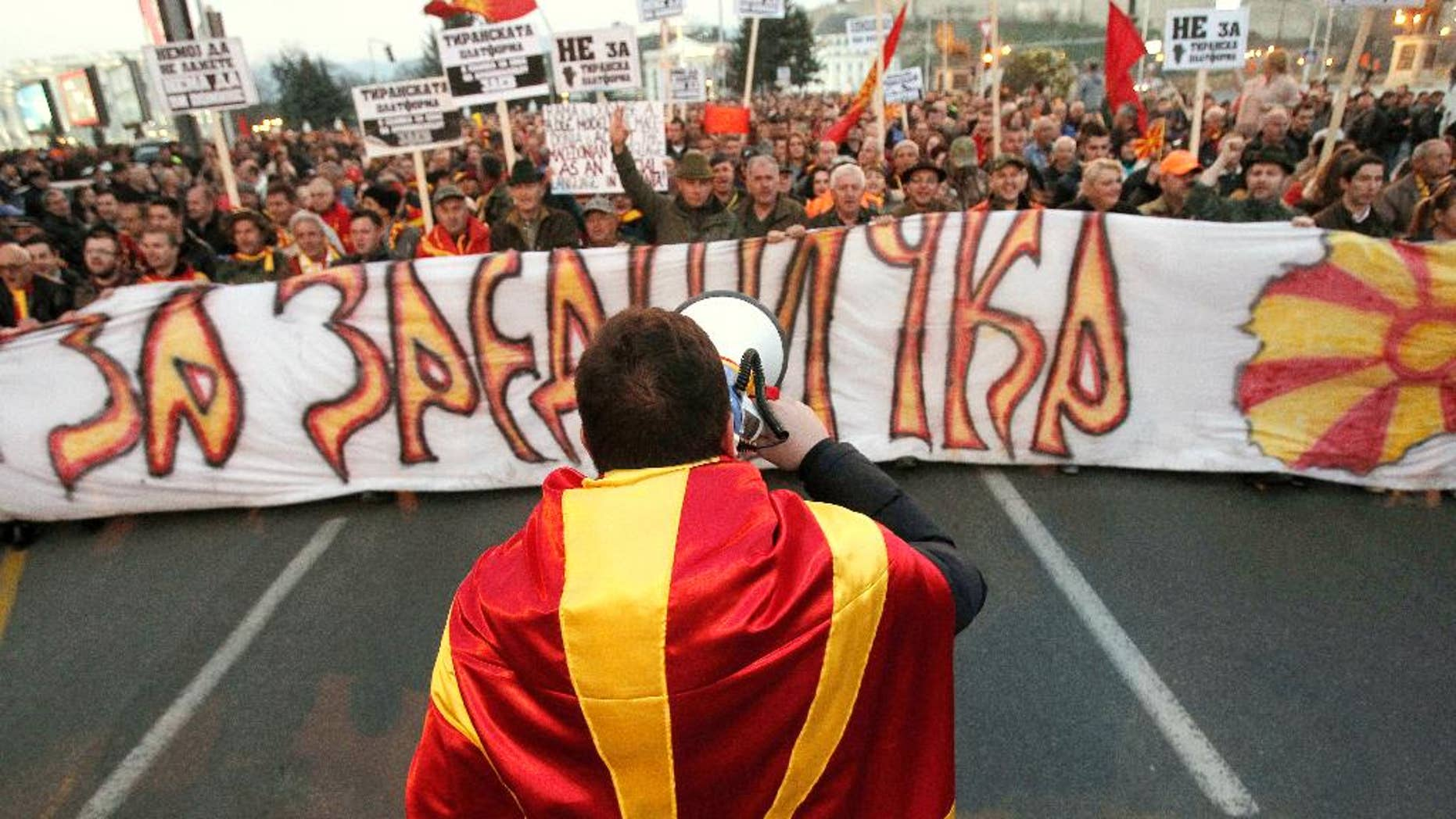 """A man wrapped in a Macedonian flag leads a protest march through a street in Skopje, Macedonia, Thursday, March 16, 2017. Thousands of Macedonians protested peacefully for a third week in the capital Skopje and other cities, against the designation of Albanian as a second official language nationwide. The banner reads in Macedonian """"For Common Macedonia"""". (AP Photo/Boris Grdanoski)"""