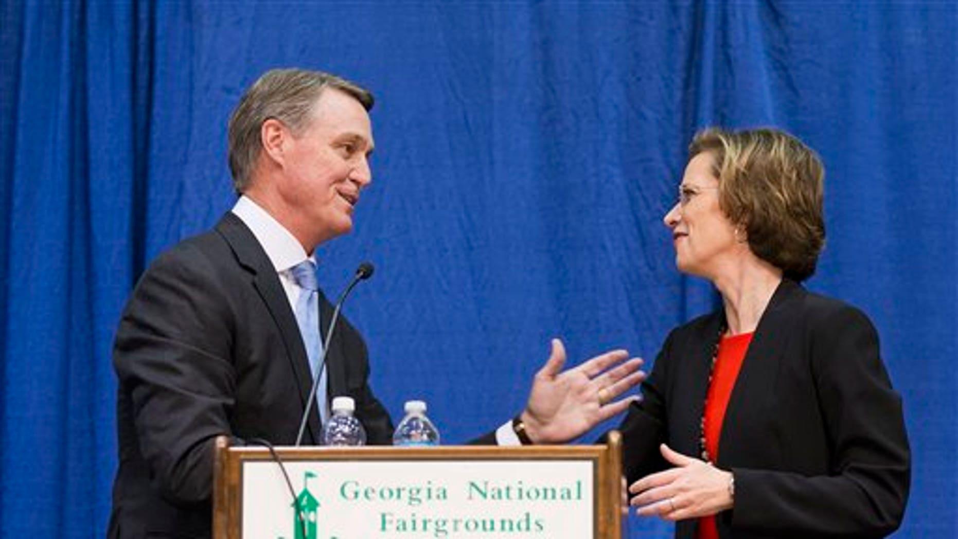 Georgia Democratic candidate for U.S. Senate Michelle Nunn, right, shakes hands with Republican candidate David Perdue following a debate, Tuesday, Oct. 7, 2014, in Perry, Ga. (AP Photo/David Goldman)