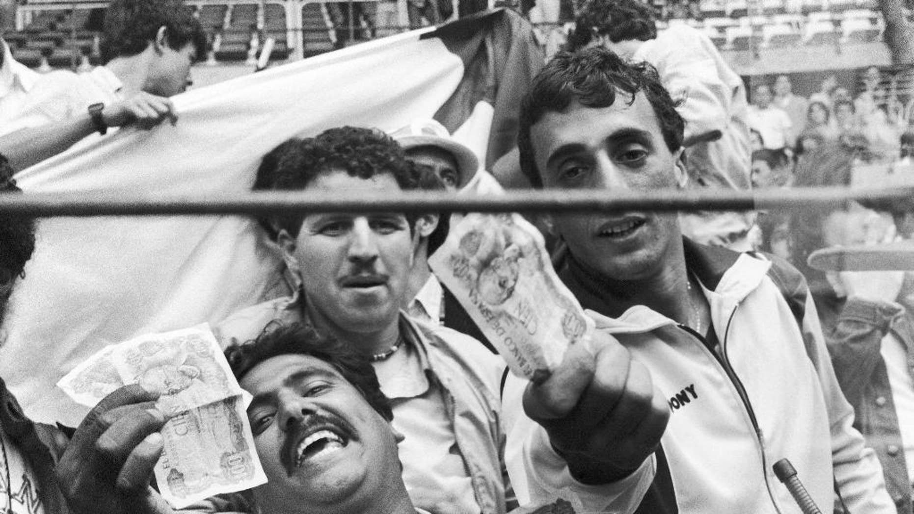 FILE -  In this June 25, 1982 file photo, Algerian soccer supporters show money to photographers, in Gijon, Spain, after the World Cup soccer match between West Germany and Austria. On this day:  West Germany beat Austria 1-0, a result that meant both teams progressed to the next round at Algeria's expense. After West Germany took an early lead, the game ran its bland course to conclusion to the ire of the watching Algerians. (AP Photo/File)