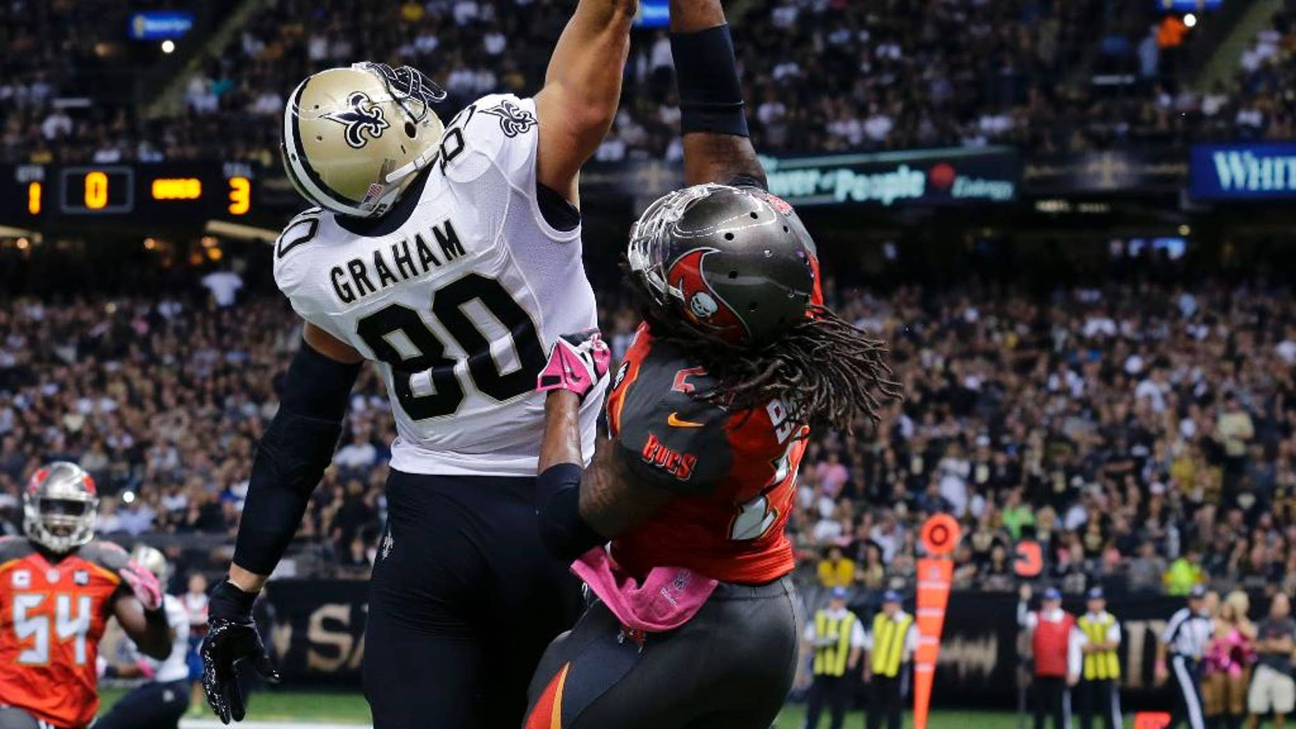 New Orleans Saints tight end Jimmy Graham (80) leaps for an overthrown pass as Tampa Bay Buccaneers strong safety Mark Barron defends in the first half of an NFL football game in New Orleans, Sunday, Oct. 5, 2014. (AP Photo/Bill Haber)