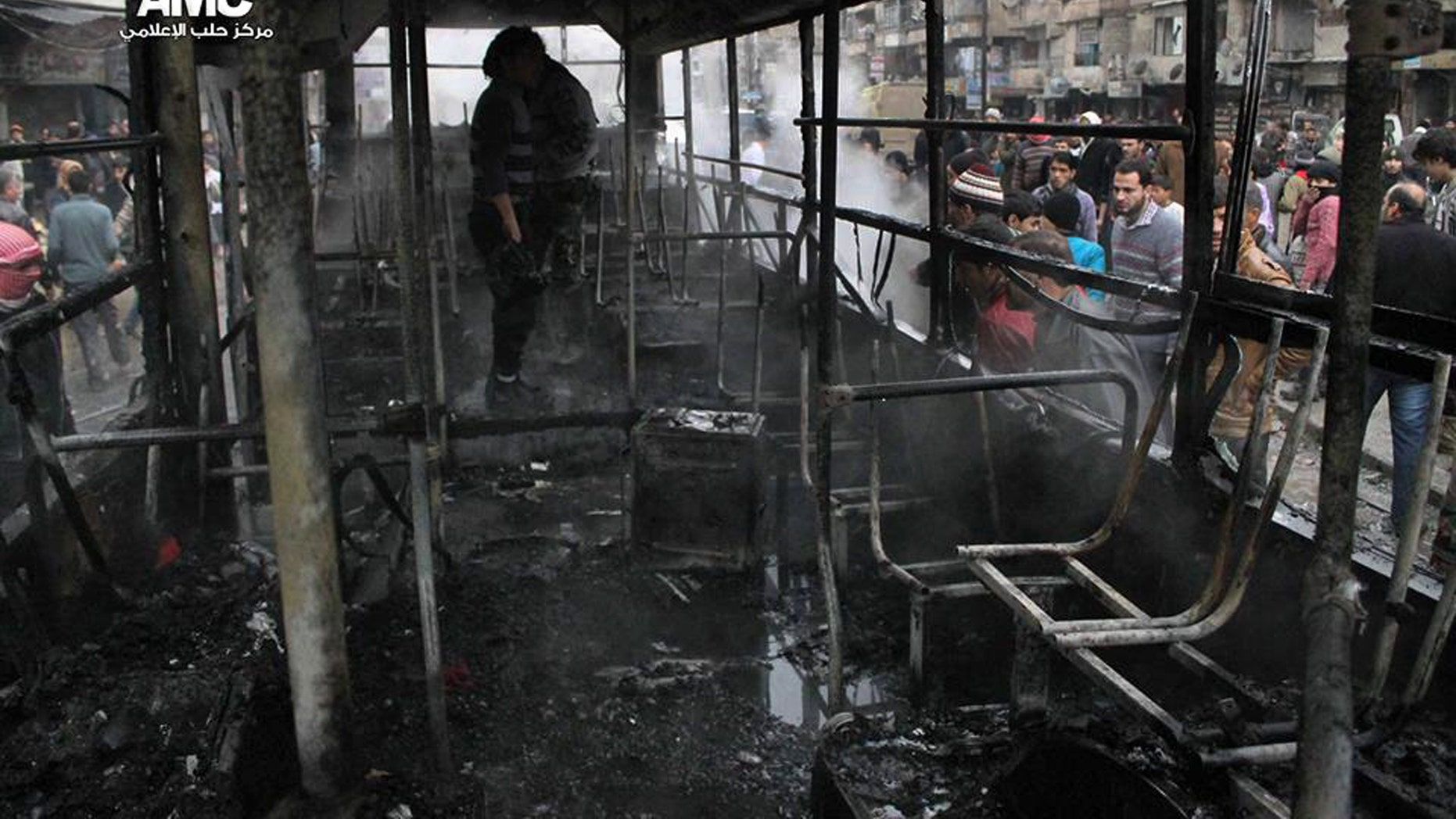 This citizen journalism image provided by Aleppo Media Center AMC which has been authenticated based on its contents and other AP reporting, shows Syrians inspecting a burnt bus after a missile fired by Syrian government aircraft hit the vehicle in the rebel-held neighborhood of al-Bab in Aleppo, Syria, Tuesday, Dec. 31, 2013. The bus was full of people when it was struck, setting it on fire and killing several people, activists said. (AP Photo/Aleppo Media Center AMC)