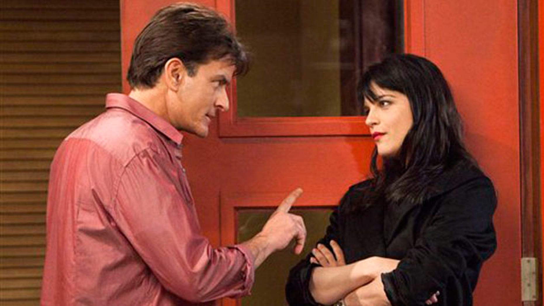 """This file publicity image provided by FX shows Charlie Sheen as Charlie Goodson and Selma Blair as Kate Wales in a scene from the new comedy """"Anger Management."""""""