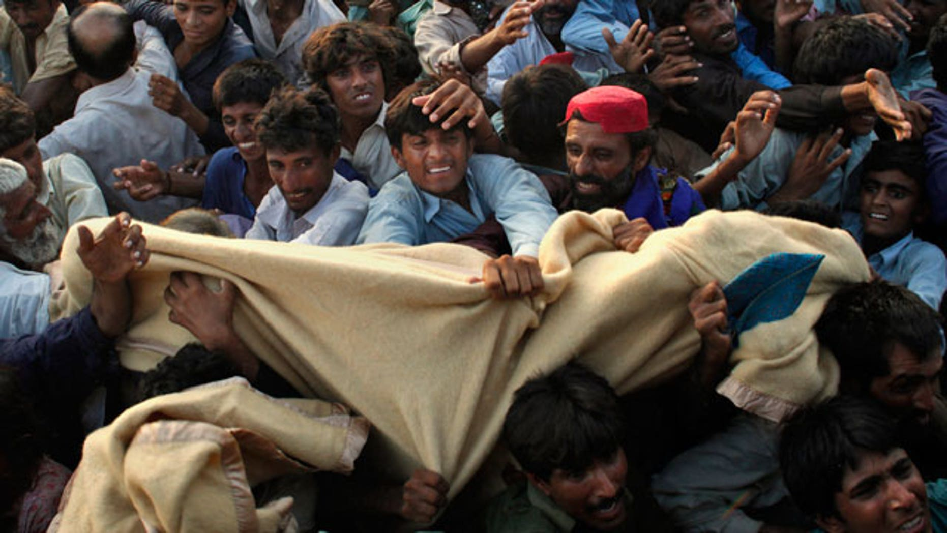 Pakistanis displaced by flooding fight for blankets during an aid distribution by the Pakistani Air Force at a temporary camp set up for residents who had to flee their homes in Sukkar, Sindh Province, southern Pakistan, Thursday, Aug. 19, 2010.