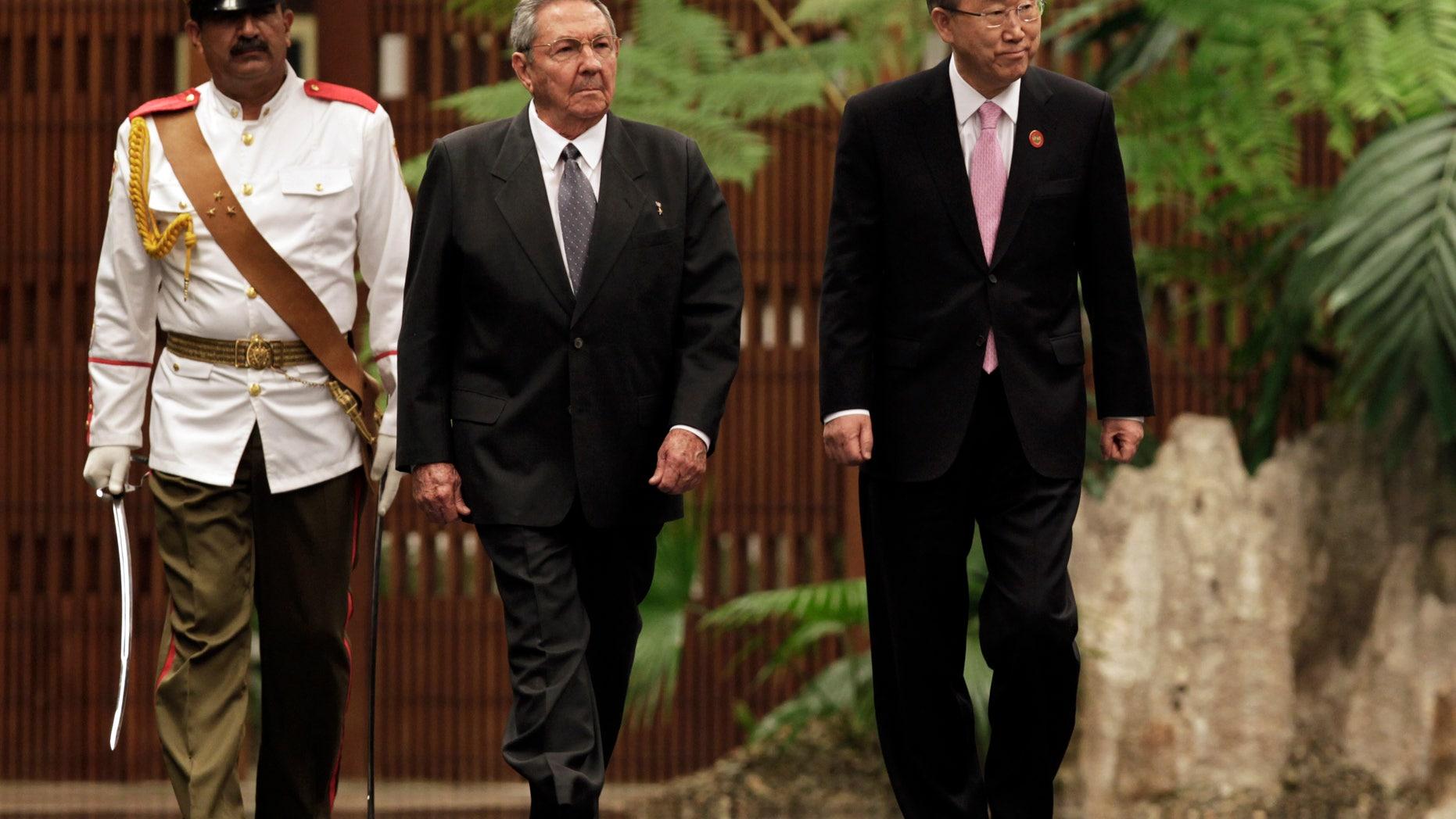 Cuba's President Raul Castro, left center, and U.N. Secretary General Ban Ki-moon, right, review an honor guard at the Revolutionary Palace in Havana, Cuba, Monday, Jan. 27, 2014. (AP Photo/Pool)
