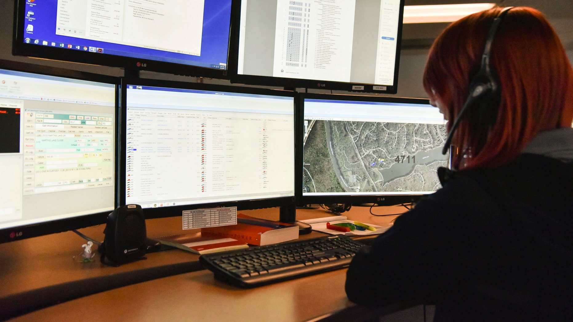 A 911 dispatcher in Roswell, Ga., works with a variety of screens while handling a call, March 15, 2018.