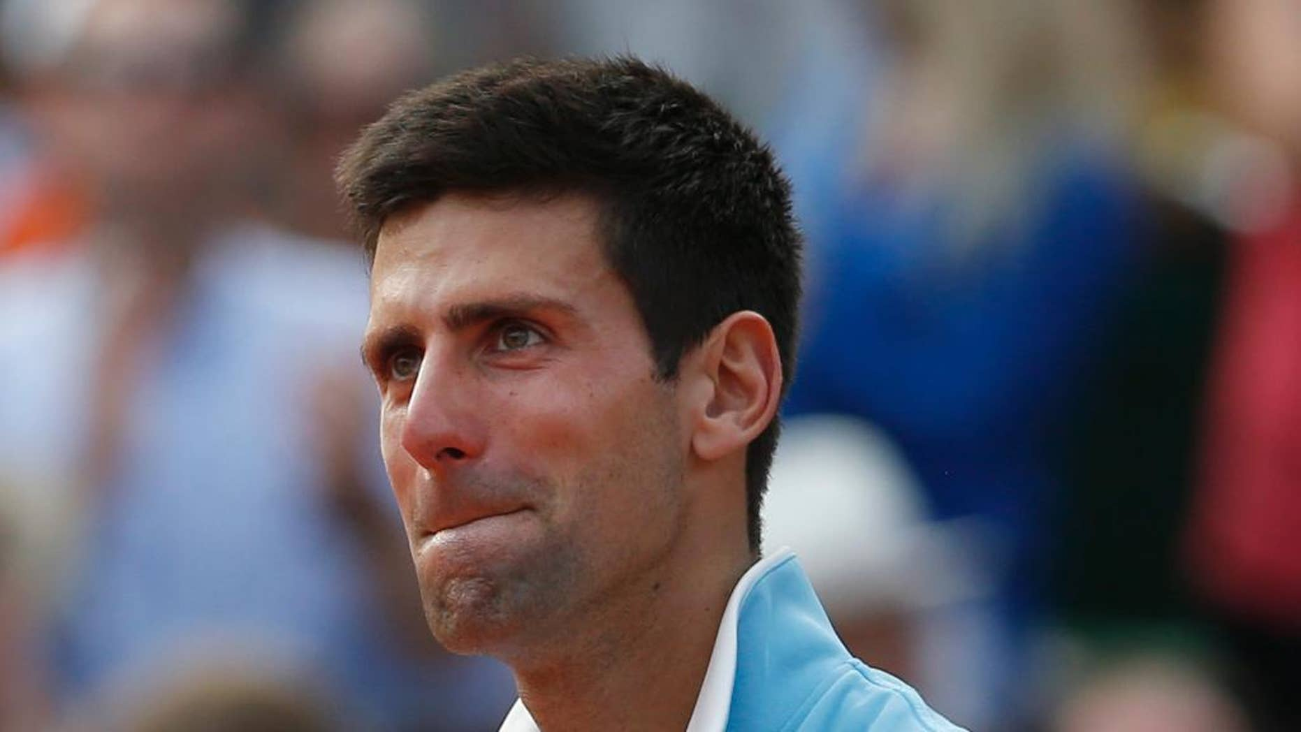 Serbia's Novak Djokovic holds the runner-up trophy after losing the final of the French Open tennis tournament against Spain's Rafael Nadal at the Roland Garros stadium, in Paris, France, Sunday, June 8, 2014. Nadal won in four sets 3-6, 7-5, 6-2, 6-4. (AP Photo/Darko Vojinovic)