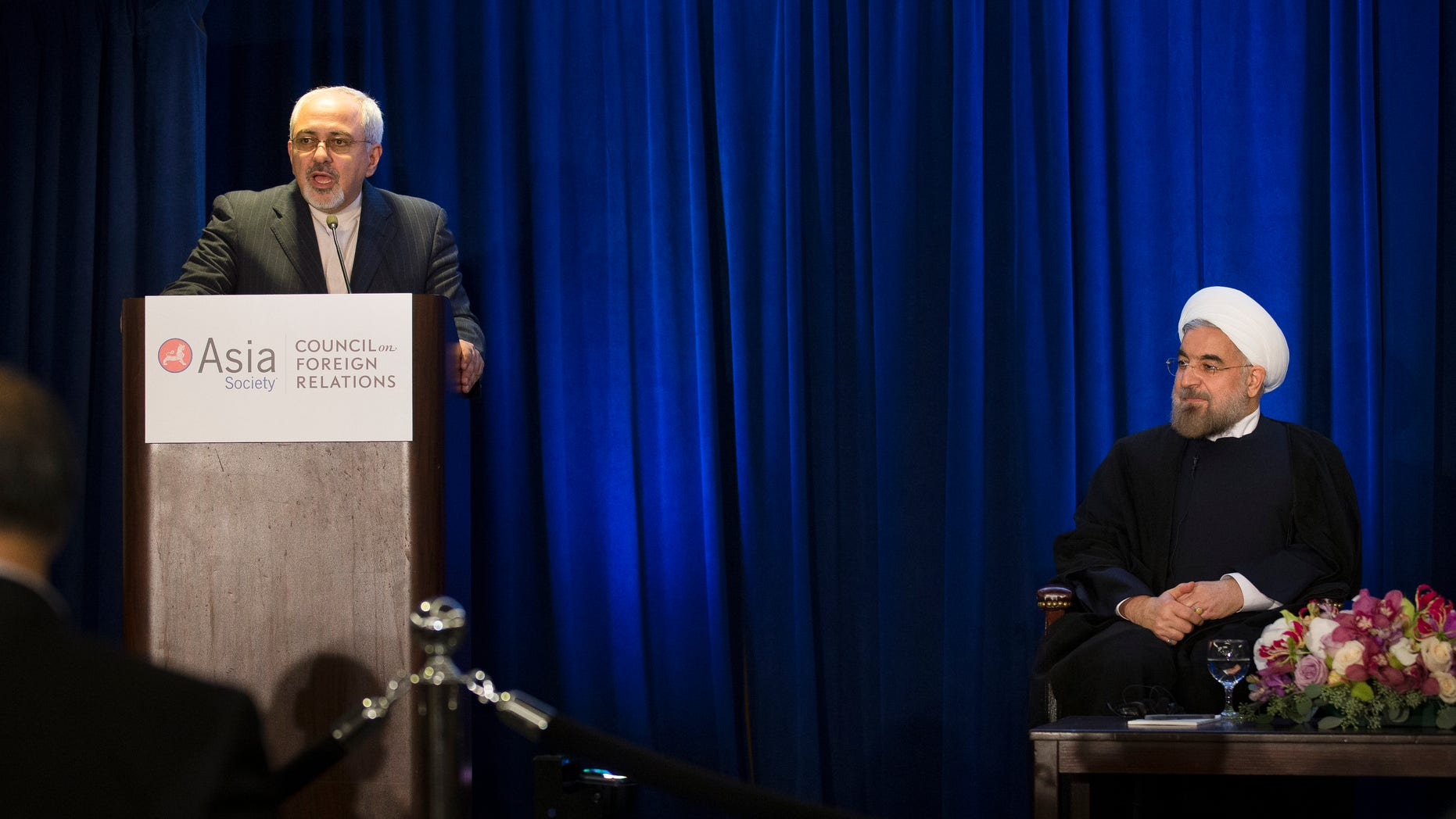 FILE - In this Thursday, Sept. 26, 2013, file photo,  Iranian President Hassan Rouhani, right, listens as Iranian Foreign Minister Mohammad Javad Zarif, left, updates the audience on the results of his bilateral meeting with U.S. Secretary of State John Kerry, during a address and discussion hosted by the Asia Society and the Council on Foreign Relations at the Hilton Hotel in New York. Iran has suddenly gone public with a significant concession just days ahead of a new round of talks with six world powers that begin Wednesday, Nov. 20, 2013 in Geneva. It still insists that it has a right to enrich uranium, but it now says that the six no longer need to publicly acknowledge its claim, opening a way to sidestep the dispute and focus on more practical steps both sides can agree on. (AP Photo/John Minchillo, File)