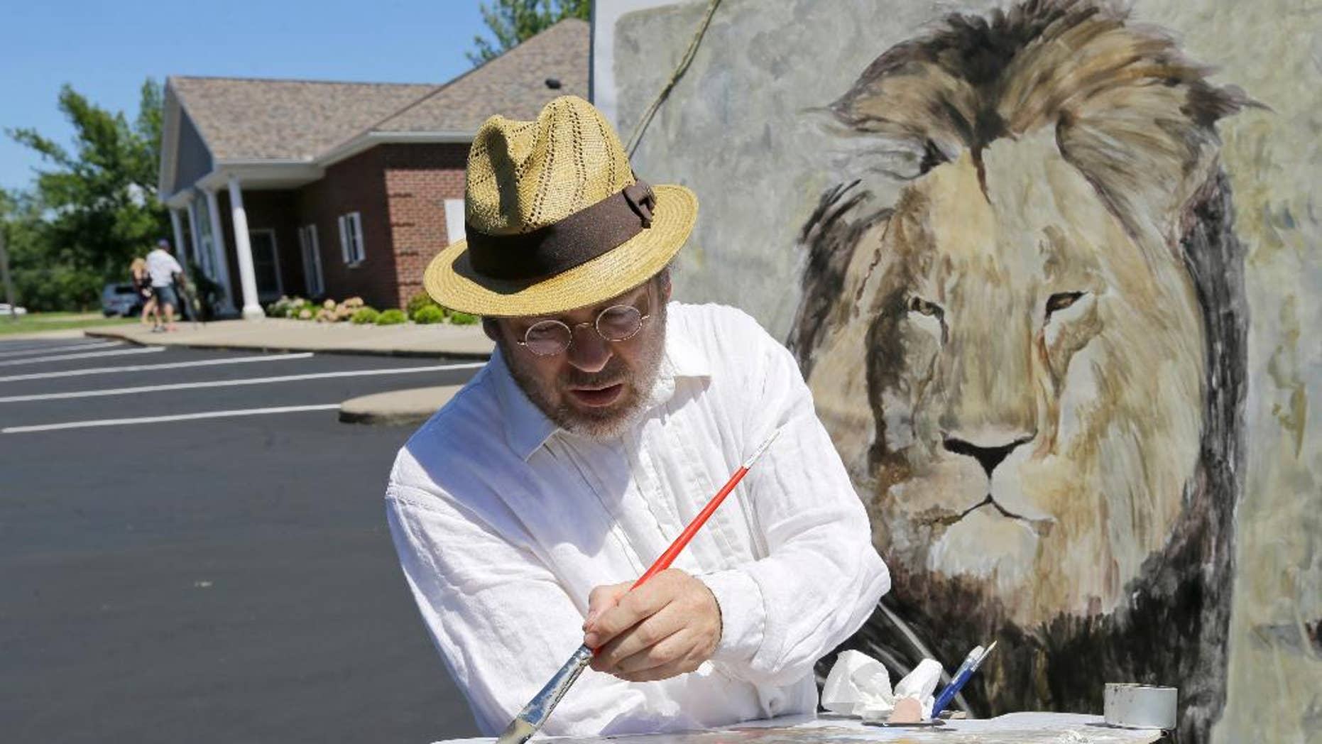 FILE - In this July 29, 2015, file photo, artist Mark Balma paints a mural of Cecil, a well-known lion killed by Minnesota dentist Walter Palmer during a guided bow hunting trip in Zimbabwe, as part of a silent protest outside Palmer's office in Bloomington, Minn. Palmer participated in an interview Sunday, Sept. 6, in which he disputed some accounts of the hunt, expressed agitation at the animosity directed at those close to him and said he would be back at work within days. (AP Photo/Ann Heisenfelt, File)