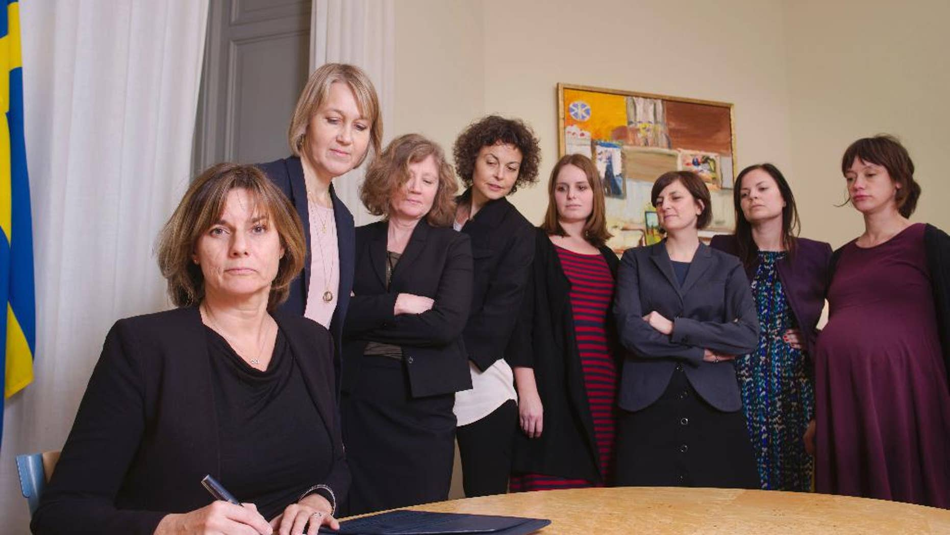 In this handout photo provided by the Swedish Government, Sweden's Deputy Prime Minister Isabella Lovin, left, signs a proposal for the Scandinavian country's new climate law in Stockholm, Friday, Feb. 3, 2017. Sweden's Deputy Prime Minister has posted on Facebook an all-woman photo including herself signing a proposal for the Scandinavian country's new climate law - a photo many online commentators have taken as a direct swipe at Donald Trump.  (Johan Schiff/Swedish Government via AP)