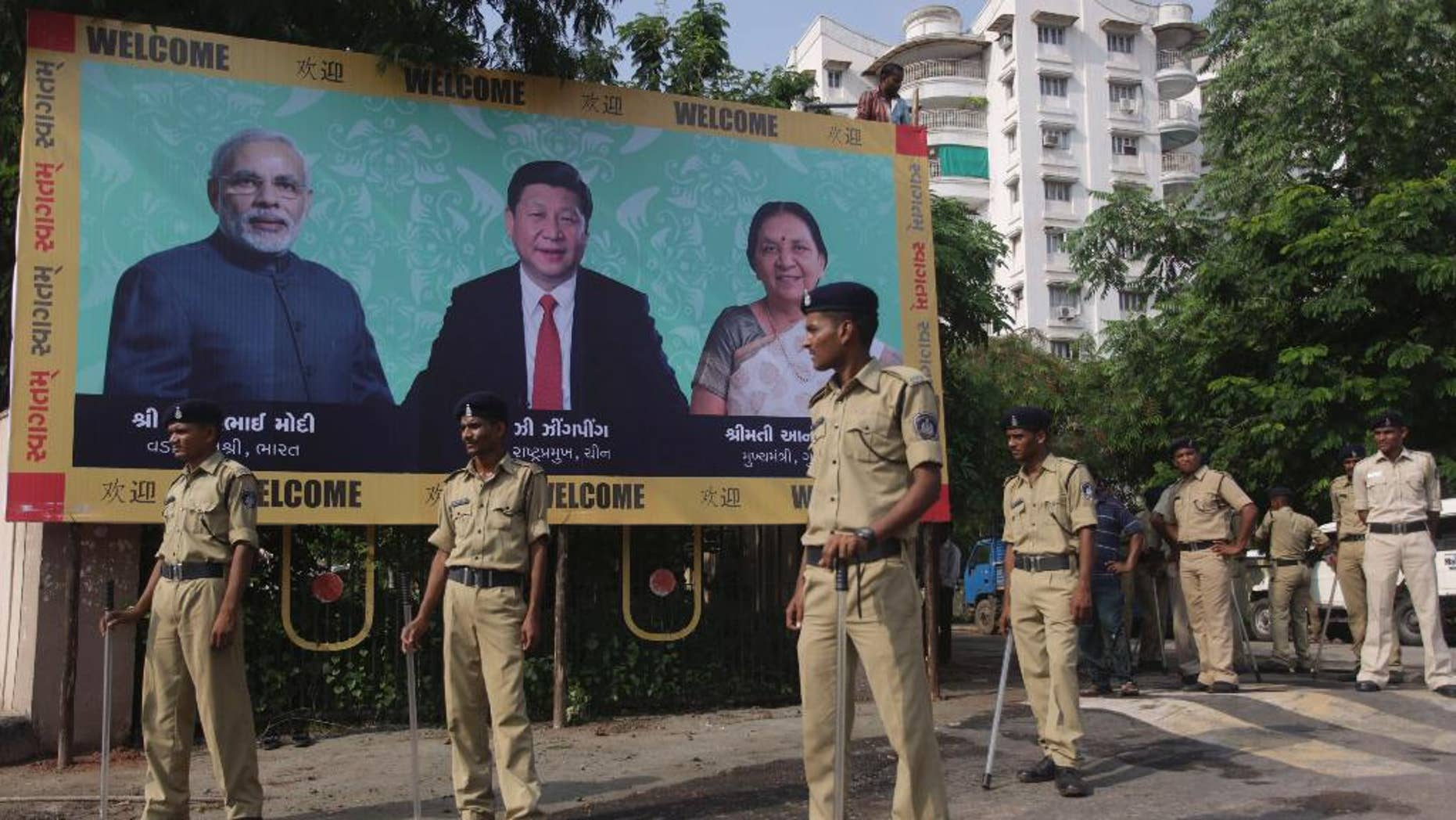 Indian policemen stand next to a welcome hoarding being erected ahead of an anticipated visit by Chinese President Xi Jinping as they review security arrangements in Ahmadabad, India, Monday, Sept. 15, 2014. Jinping is expected to arrive here Wednesday on his three-day visit to India. The hoarding also features Indian Prime Minister Narendra Modi, left and Gujarat state Chief Minister Anandiben Patel, right. (AP Photo/Ajit Solanki)