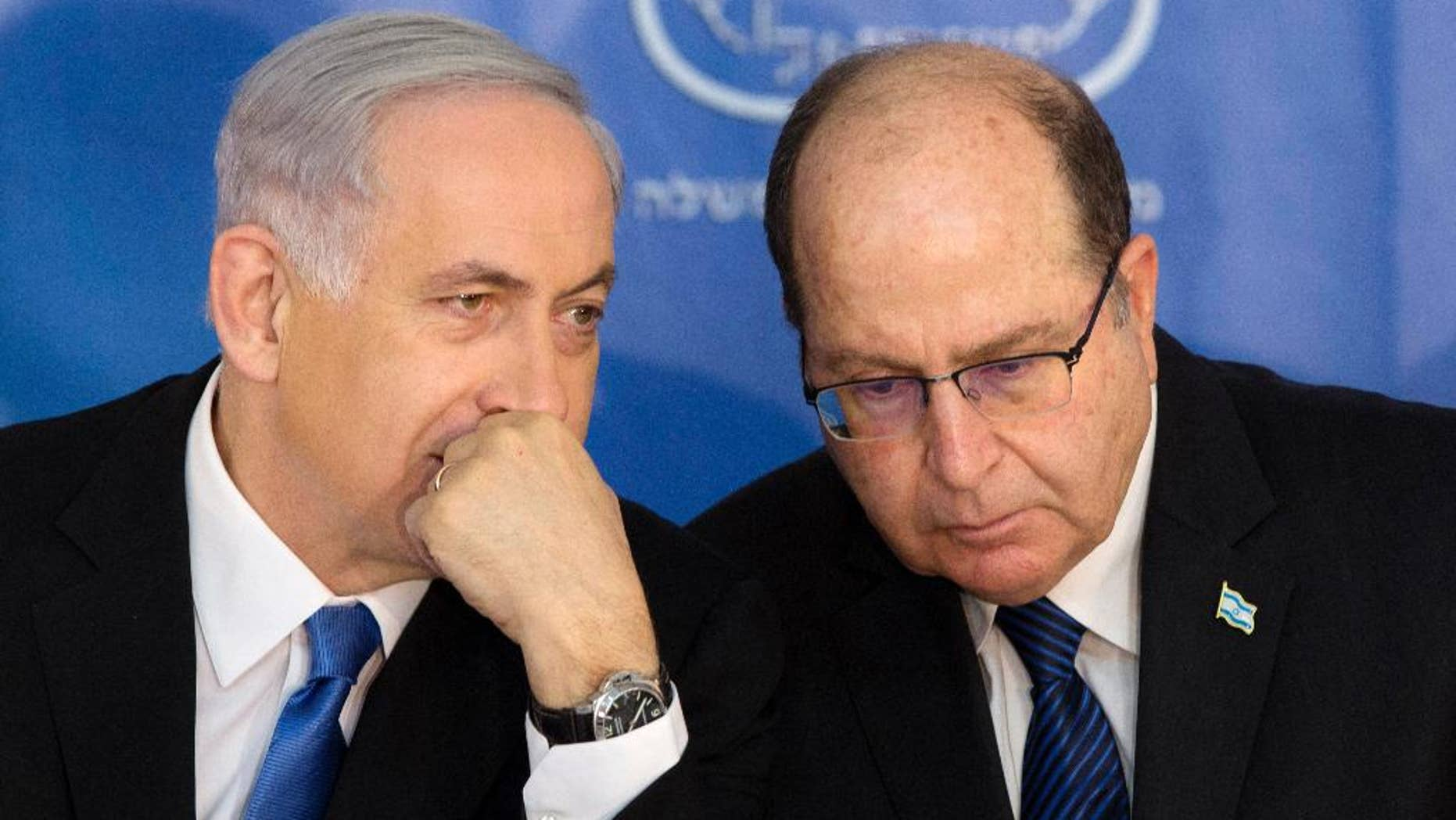 FILE - In this Monday, Feb. 16, 2015 file photo, Israeli Prime Minister Benjamin Netanyahu, left, speaks with Israel's Defense Minister Moshe Yaalon during a ceremony for new Israeli Chief of Staff Gadi Eizenkot at the Prime Minister's office in Jerusalem. Israel's newly resigned defense minister has accused Prime Minister Benjamin Netanyahu of exaggerating the country's security threats to distract attention from other issues. (AP Photo/Sebastian Scheiner, File)