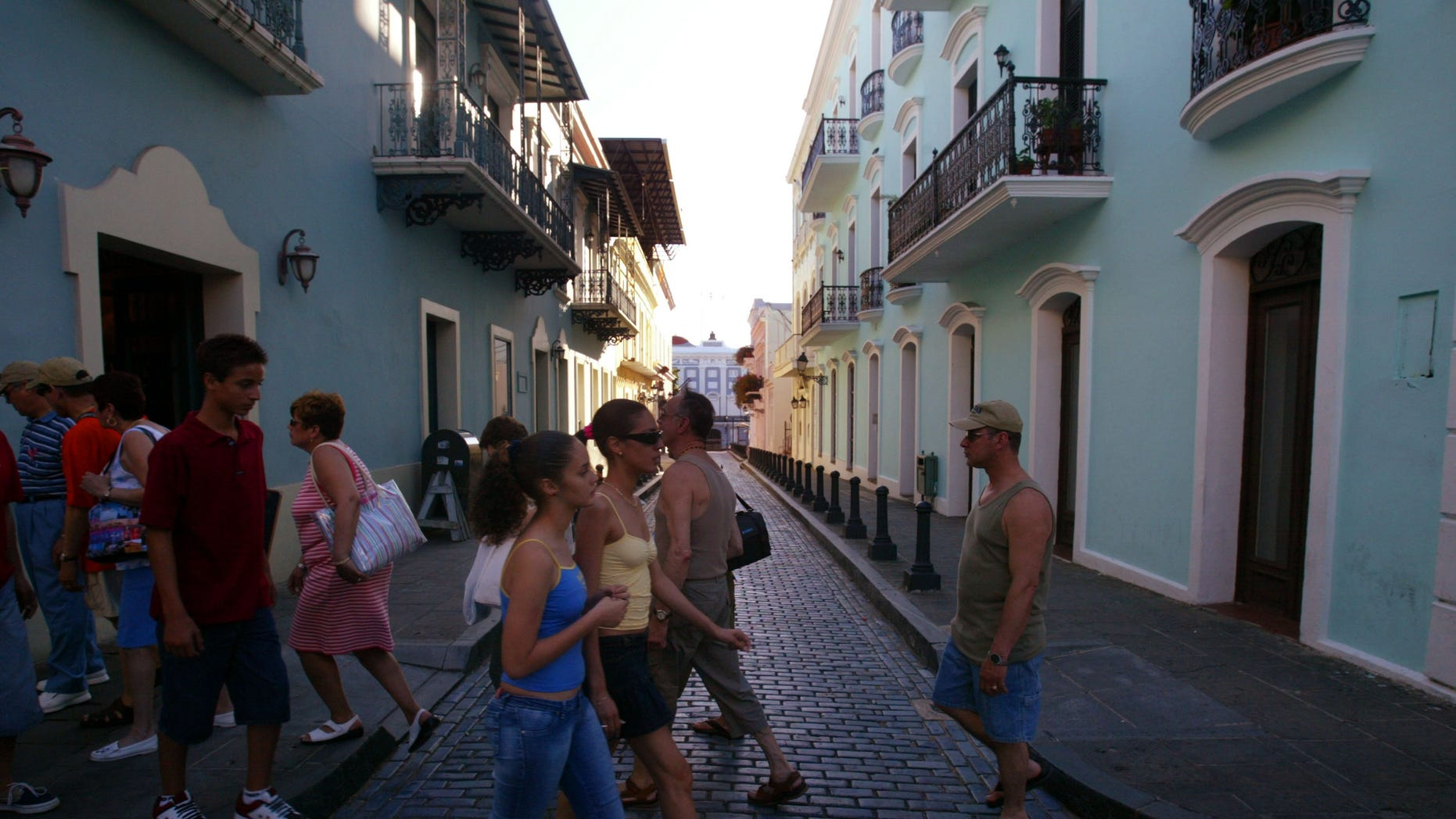 SAN JUAN, PUERTO RICO- APRIL 25: Visitors walk past colorful homes that line the cobblestoned streets April 25, 2004 in Old San Juan, the original capital city of San Juan, Puerto Rico. The old city is a historic district of seven square blocks made up of ancient buildings and colonial homes, massive stone walls and vast fortifications, sunny parks and cobblestoned streets.  (Photo by Joe Raedle/Getty Images)