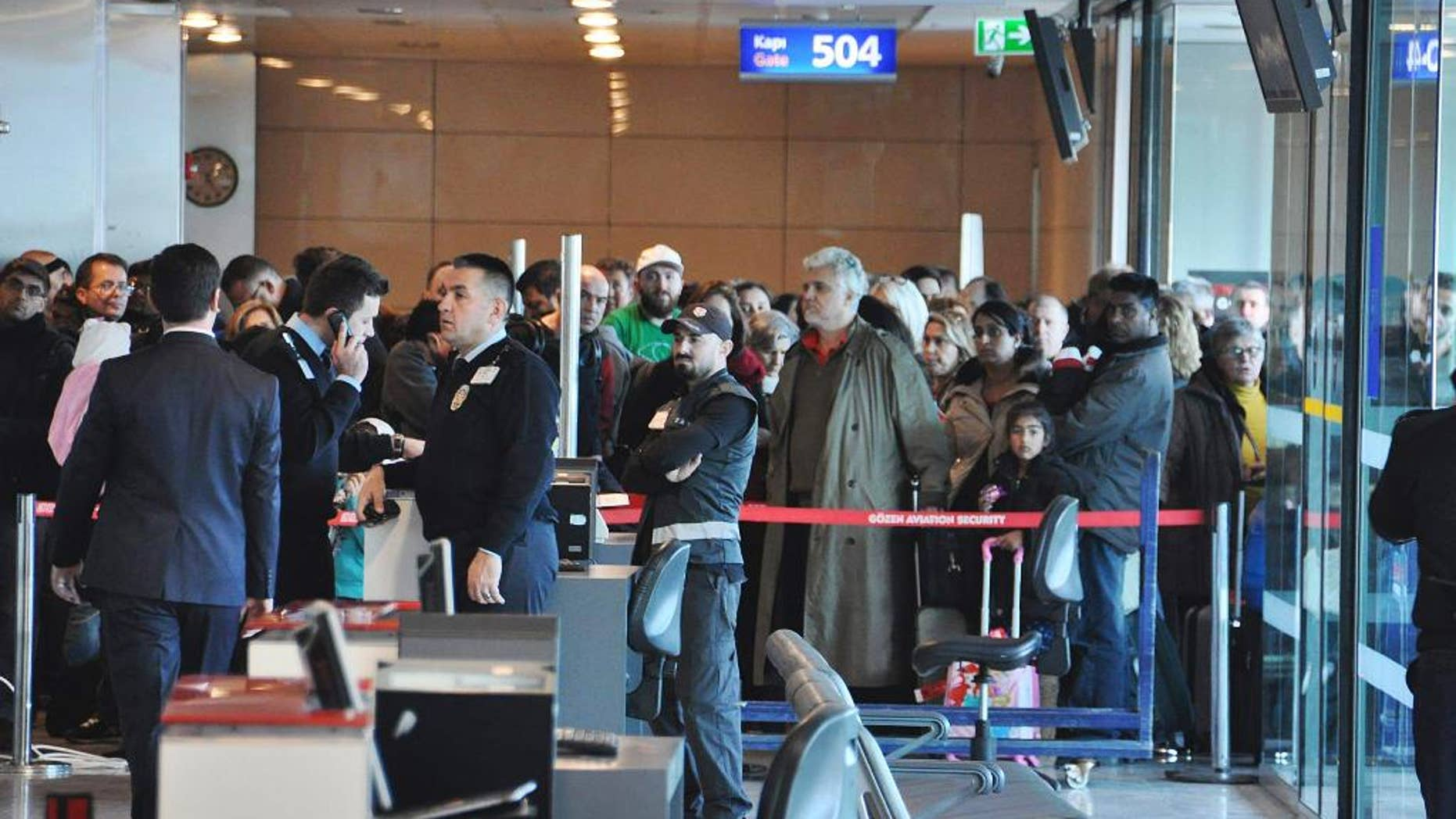 """Passengers of a Turkish Airlines flight to Toronto, Canada, wait at the boarding gate in Istanbul's Ataturk international airport, Saturday, Feb. 18, 2017. A Turkish Airlines plane in Istanbul was evacuated Saturday after a suspicious note was discovered in one of its bathrooms. The Turkish Airlines cabin crew found the words """"BOMB TO TORONTO"""" on the bathroom's wall on Flight TK-17 during its pushback from the gate, a Turkish Airlines press official told The Associated Press. (DHA-Depo Photos via AP)"""
