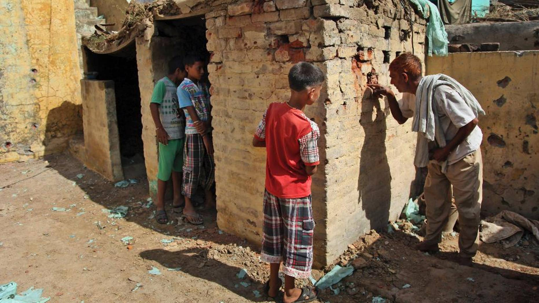 An Indian village man looks at one of the houses damaged in firing between India and Pakistan at the border area of Treava village in Arnia sector, in Jammu, India, Saturday, Oct. 11, 2014. Exchanges of fire are common along the tense and heavily guarded frontier, but this week's flare-up, which left more than 20 people dead, is the most serious violation yet of a 2003 cease-fire agreement. (AP Photo/Channi Anand)