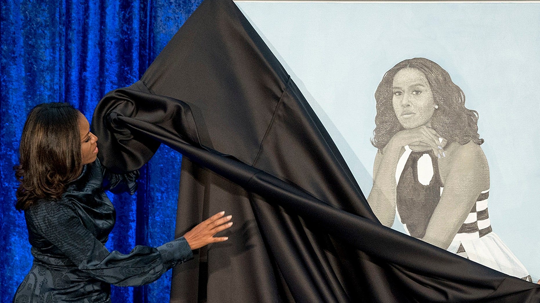 Former first lady Michelle Obama unveils her portrait at the Smithsonian's National Portrait Gallery.