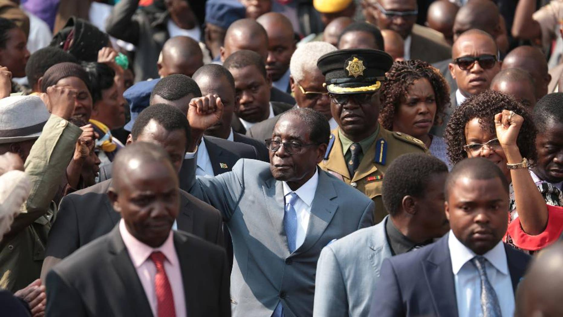 """Zimbabwean President Robert Mugabe, centre, gestures after addressing members of the Zimbabwe National Liberation War Veterans Association, at the party headquarters, in Harare, Wednesday, July, 27, 2016. Zimbabwe's 92-year-old president on Wednesday said the longtime loyalists who turned against him last week should face """"severe"""" punishment, and he vowed to stay in power for """"a long time."""" (AP Photo/Tsvangirayi Mukwazhi)"""