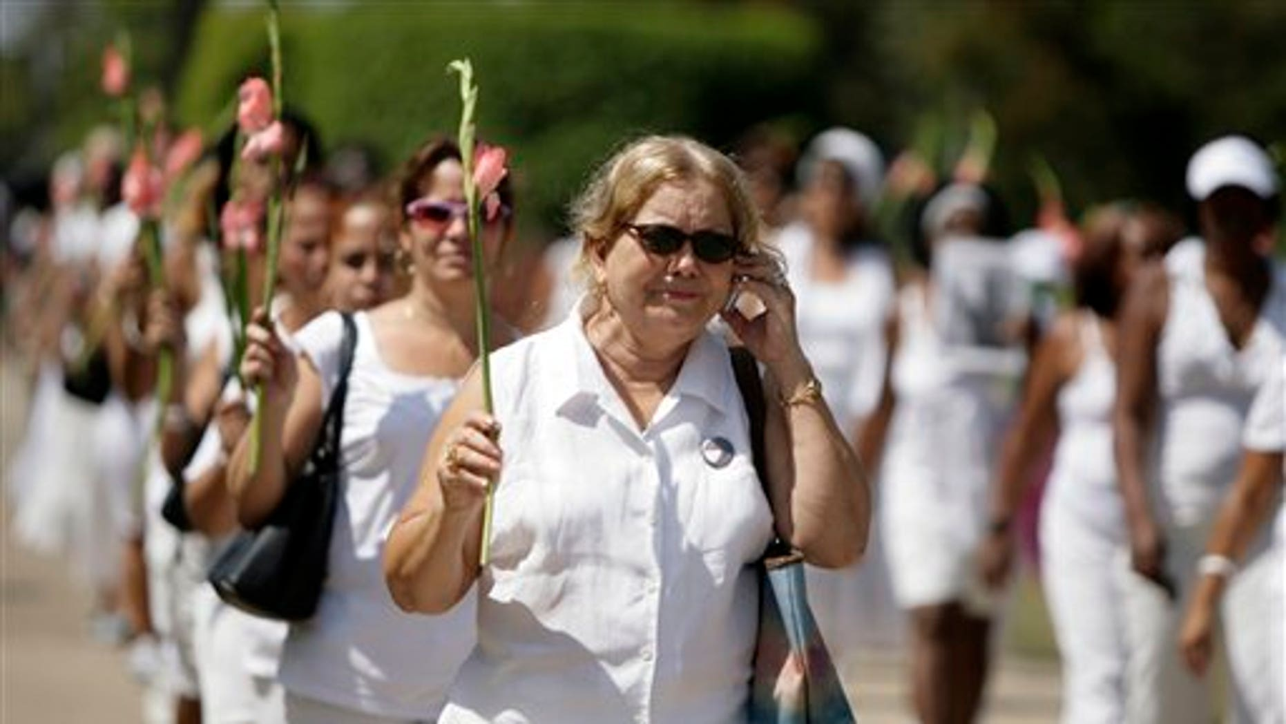 The late Laura Pollan (above, speaking on a cell phone) was leader and a founder of the dissident group Ladies in White, which held weekly marches in Havana to call for the release of political prisoners. Ladies in White included many mothers, wives and daughters of political prisoners.