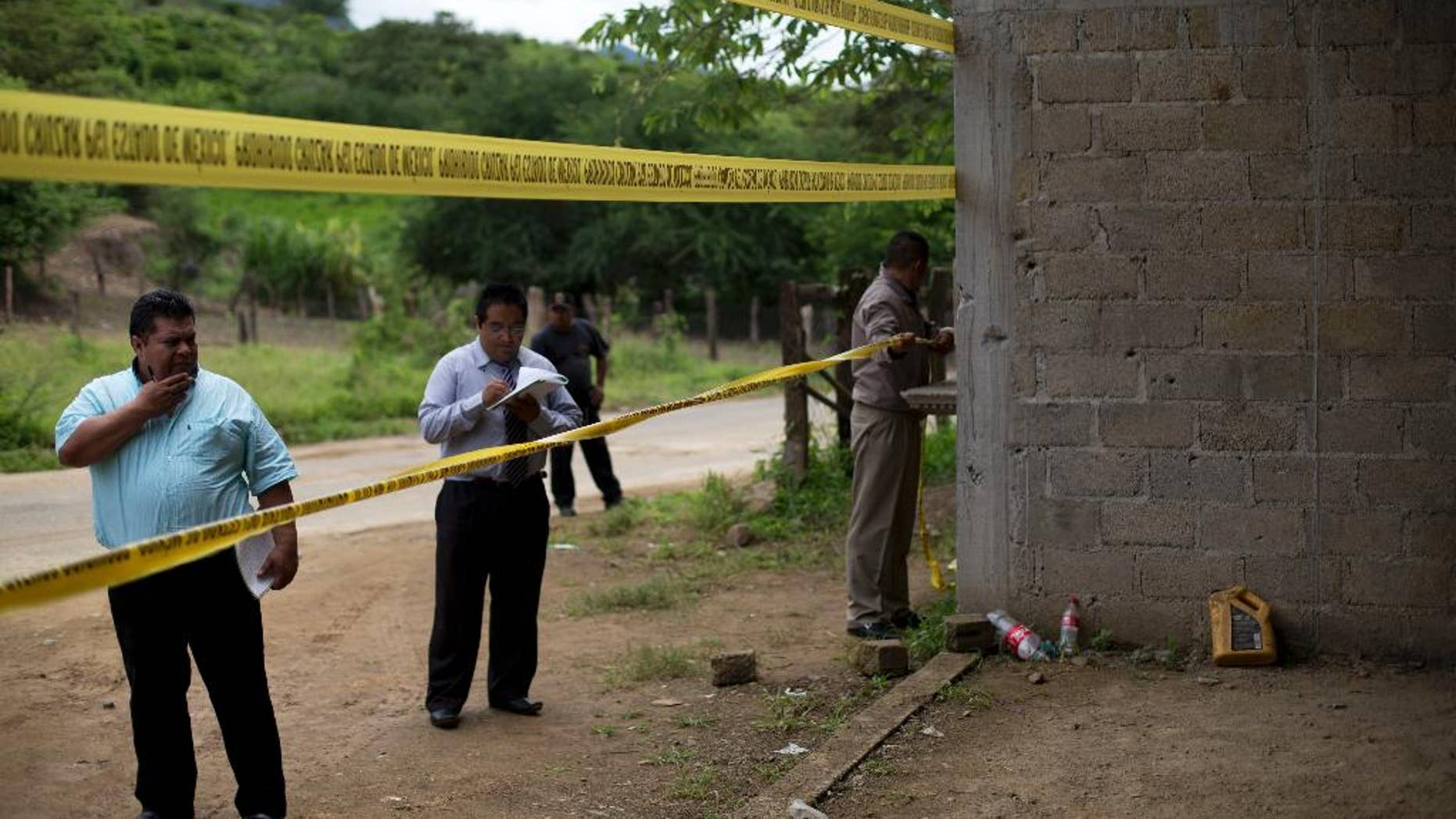 FILE - In this July 3, 2014 file photo, state authorities seal off an unfinished grain warehouse that was the site of a shootout between soldiers and alleged criminals on the outskirts of the village of San Pedro Limon in Mexico state, Mexico. Authorities in Mexico said Tuesday, July 19, 2016 they will fire seven or eight investigators and suspend 22 others for misconduct related to the 2014 army slayings of 22 suspected gang members. The country's human rights commission says soldiers killed at least a dozen of the suspects after they surrendered. (AP Photo/Rebecca Blackwell, File)