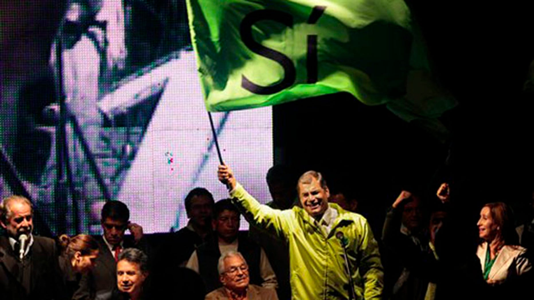 "Ecuador's President Rafael Correa, top, accompanied by members of his government and collaborators, waves a flag that reads in Spanish ""Yes,"" during a meeting in Quito, Ecuador, Saturday, May 2011. Correa declared victory after an exit poll indicated voters approved all 10 ballot questions in a referendum Saturday, an outcome critics say will tighten his grip on power, inhibit press freedom and lessen the judiciary's independence. (AP Photo/Dolores Ochoa)"