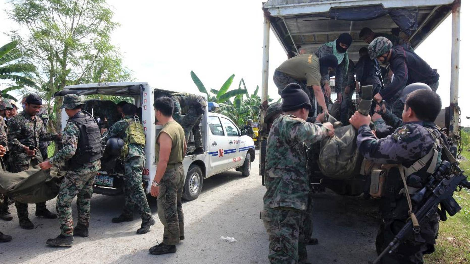 Members of the Philippine National Police Special Action Forces load bodies of police commandos into vehicles in Maguindanao, Philippines, Monday, Jan. 26, 2015. More than 40 Philippine police commandos were killed in a fierce battle with Muslim guerrillas after launching an assault in which they may have killed one of southeast Asia's most-wanted terrorists, officials said Monday. (AP Photo)