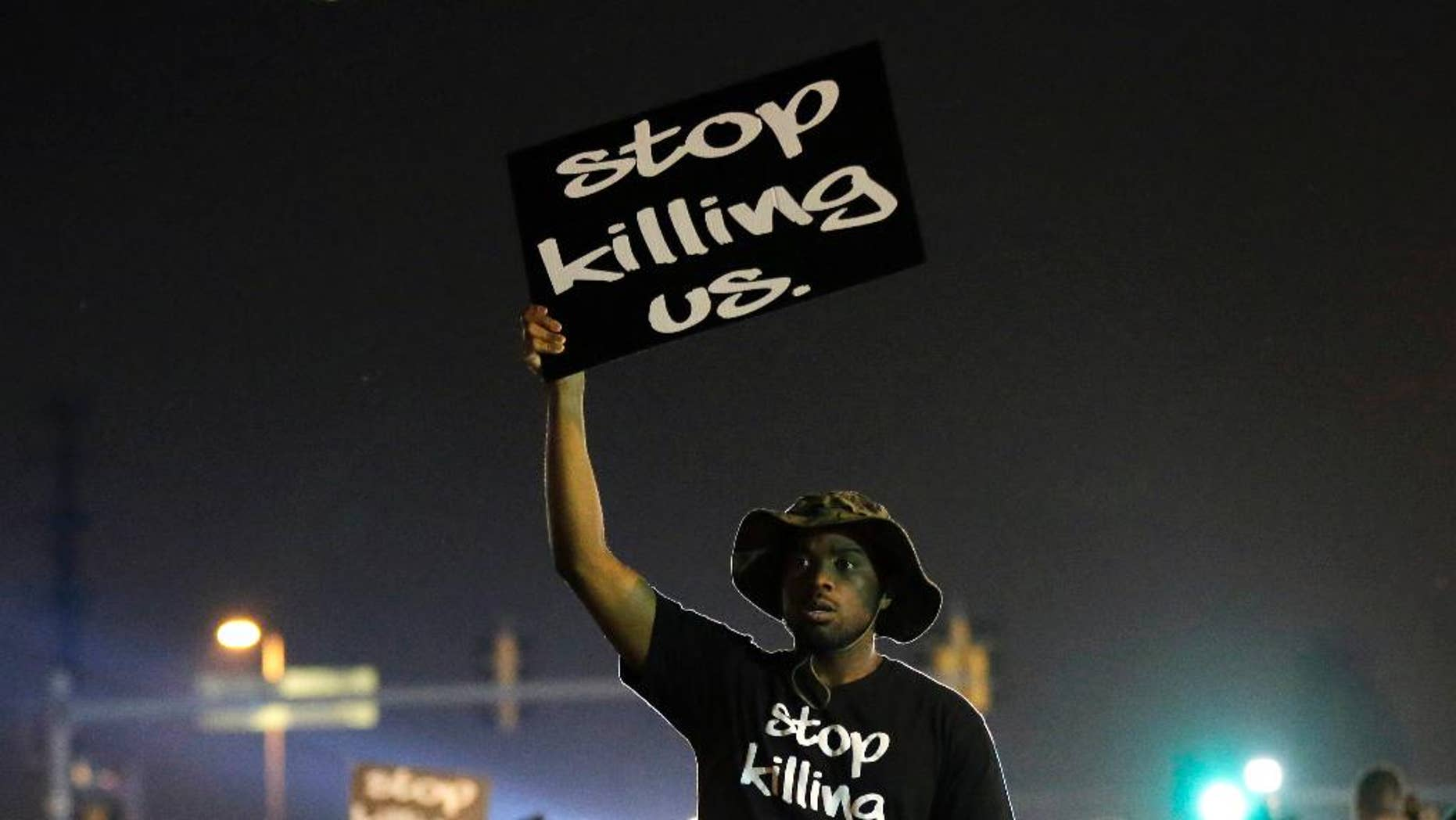 FILE - In this Aug. 18, 2014, file photo, protesters walk through the streets after a standoff with police in Ferguson, Mo. A year ago, most Americans had never heard of the St. Louis suburb called Ferguson. But after a white police officer fatally shot a black 18-year-old in the street, the name of the middle-class community quickly became known around the world. (AP Photo/Charlie Riedel, File)