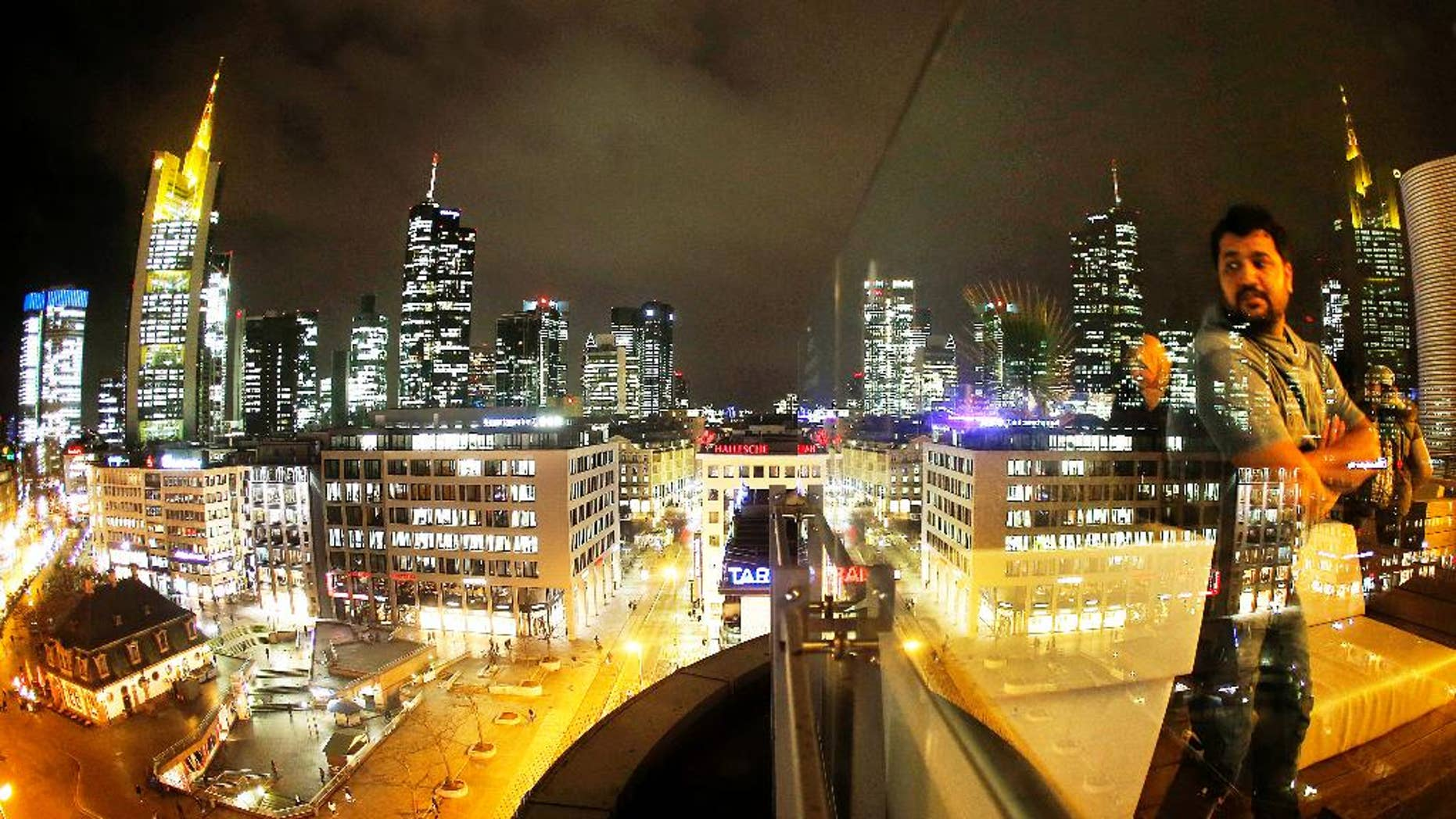 The buildings of the banking district are reflected in a glass railing while a man watches from a skyline outdoor restaurant in Frankfurt, Germany, Wednesday, Jan. 4, 2017. (AP Photo/Michael Probst)