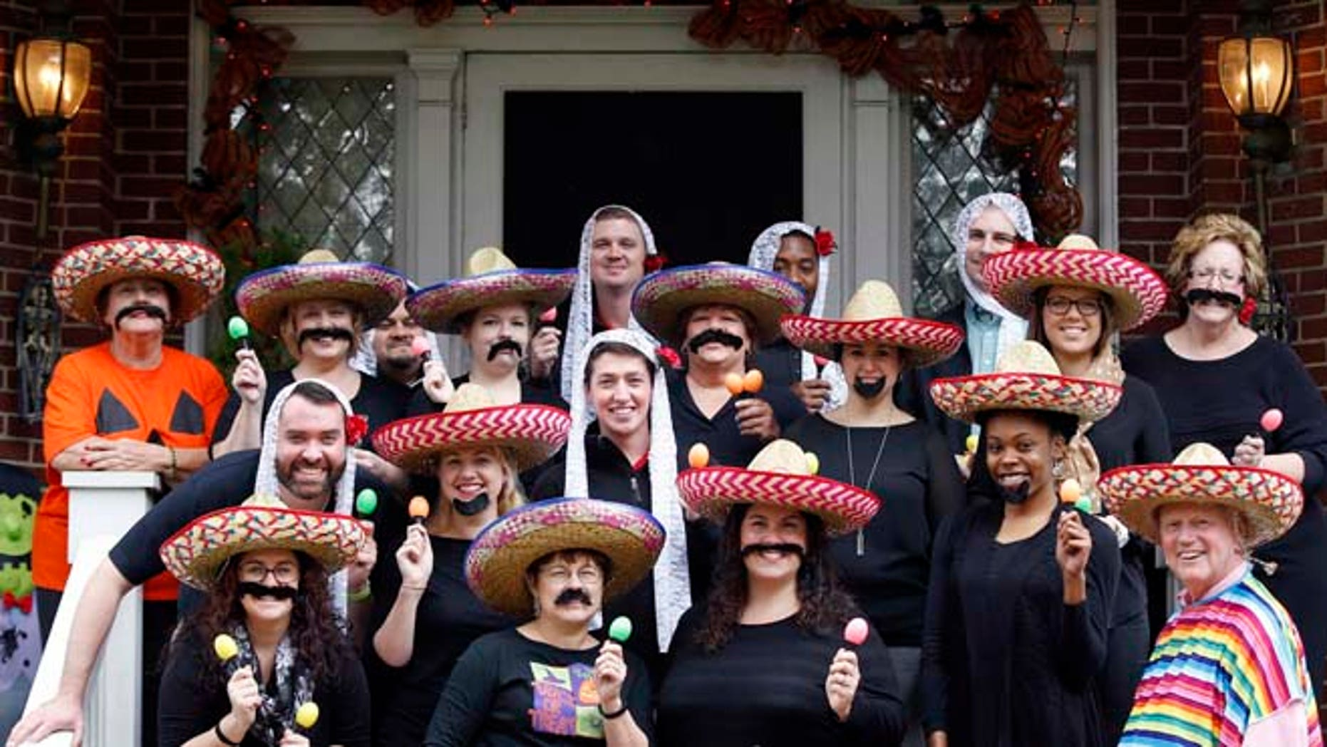 In this Oct. 28, 2015 photo, University of Louisville James Ramsey, lower right, and his wife, Jane, upper left, host a Halloween party in Louisville, Ky. The University of Louisville has apologized after the photo surfaced showing Ramsey among staffers dressed in stereotypical Mexican costumes. (Scott Utterback/The Courier-Journal via AP) NO SALES; MAGS OUT; NO ARCHIVE; MANDATORY CREDIT