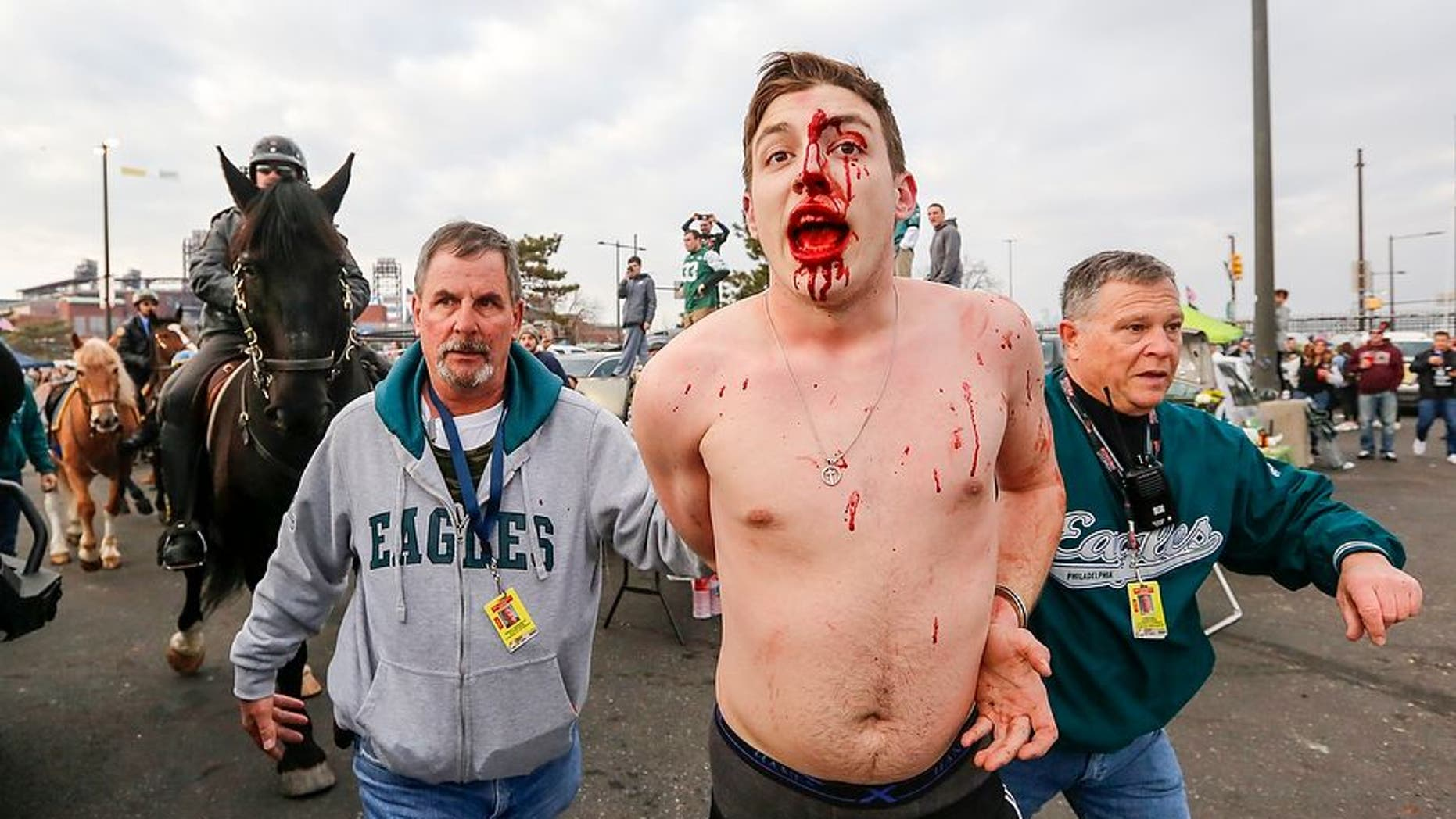 A bloodied fan was arrested by police after a massive fight broke out between Eagles tailgating fans and cops hours before the NFC Championship game with the Minnesota Vikings. (Andrew Mills/NJ Advance Media via AP)