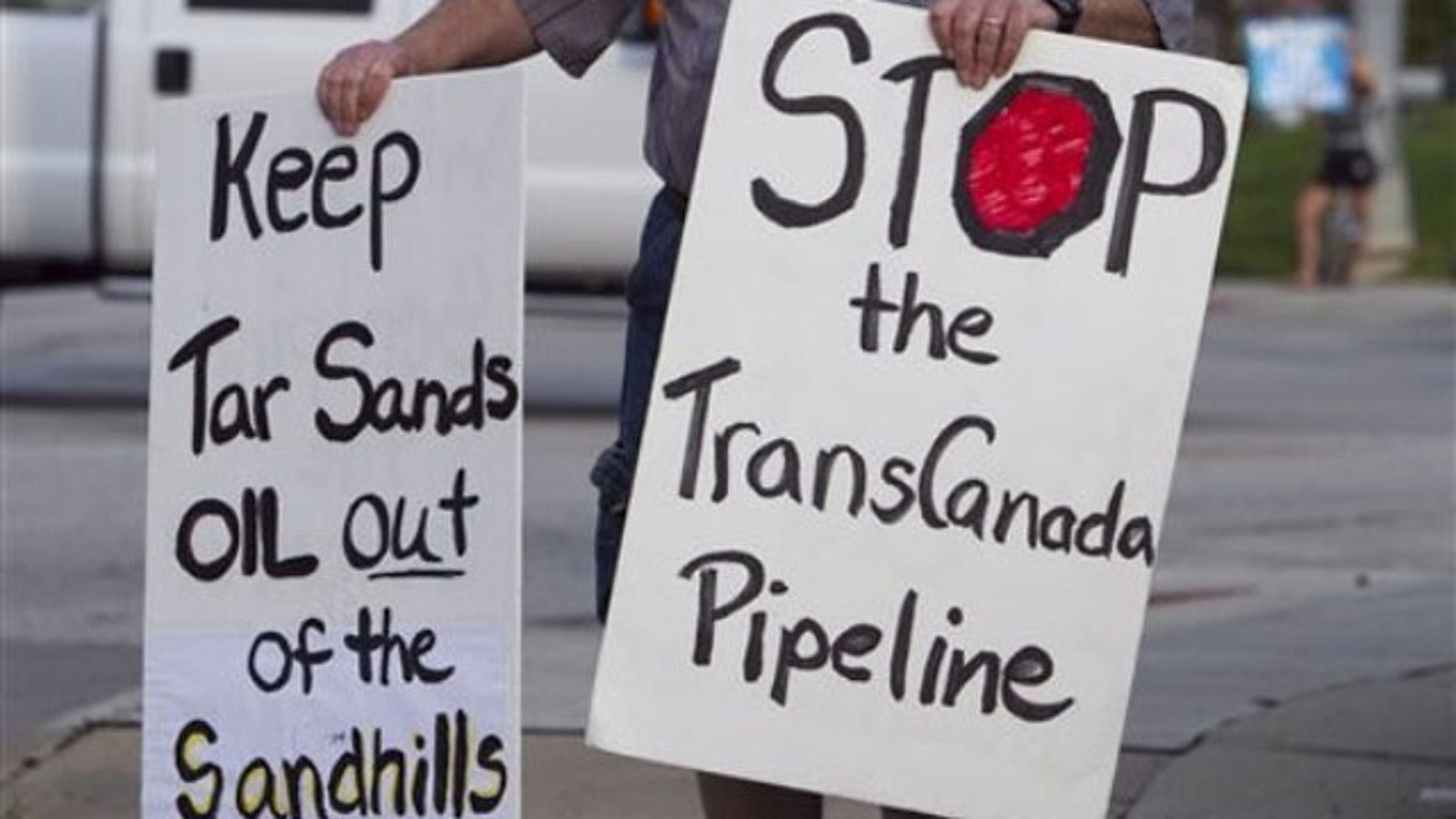 File: Sept. 21, 2010: An unidentified protester opposed to the Keystone XL pipeline carries signs, in Omaha, Neb.