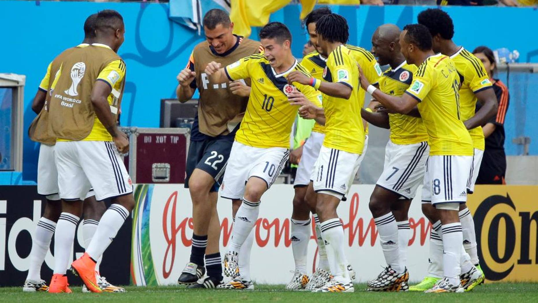 Colombia's James Rodriguez (10) celebrates with his teammates after scoring the opening goal during the group C World Cup soccer match between Colombia and Ivory Coast at the Estadio Nacional in Brasilia, Brazil, Thursday, June 19, 2014.  (AP Photo/Sergei Grits)